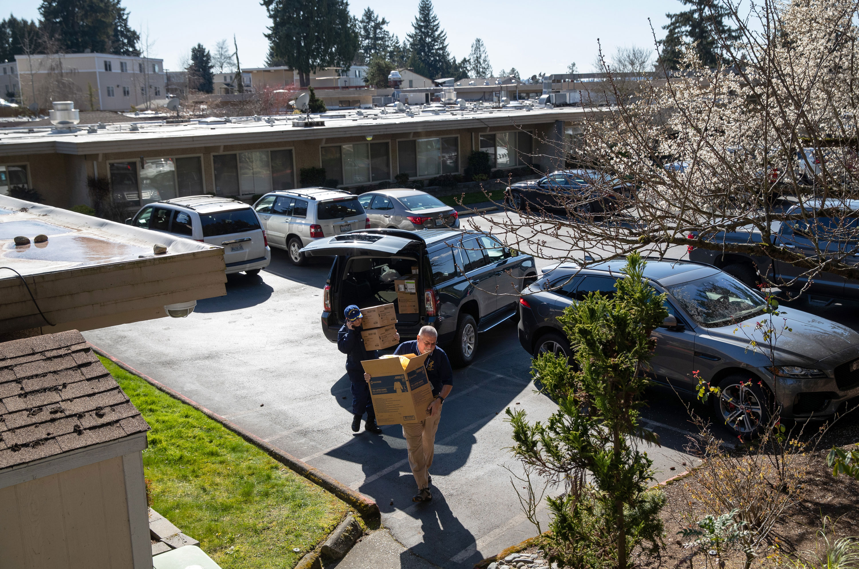 U.S. Federal health workers carry boxes into the Life Care Center nursing home on March 09, 2020 in Kirkland, Washington.