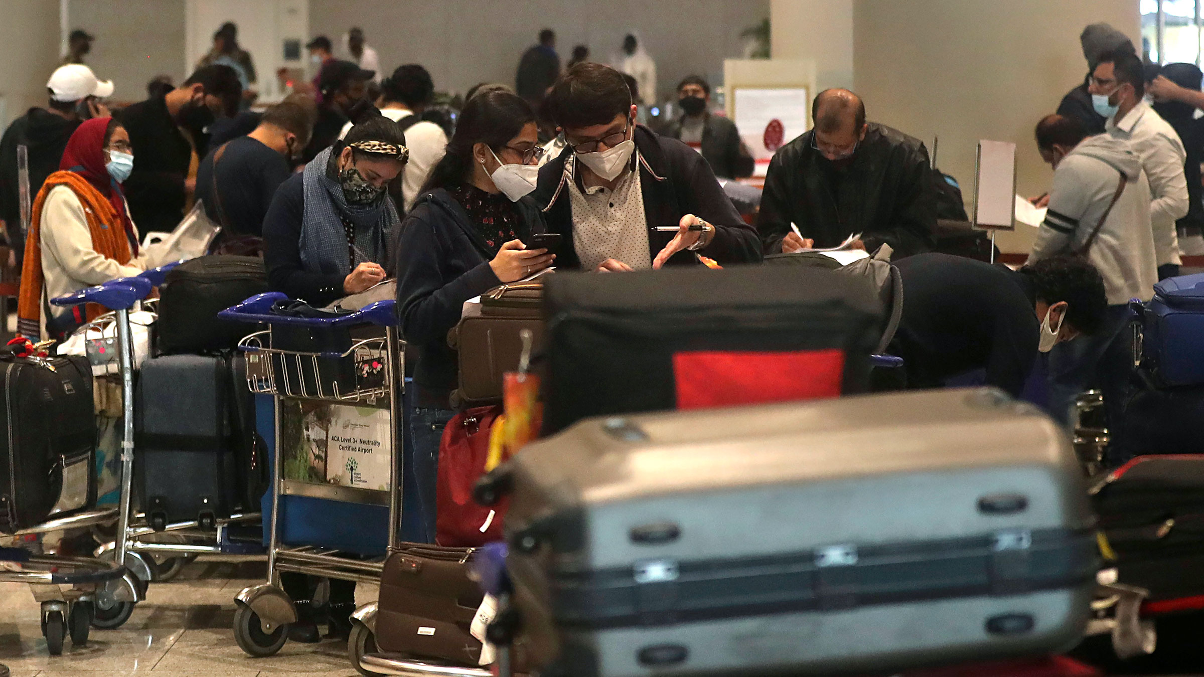 Passengers arriving from United Kingdom fill in forms with their travel details at Chhatrapati Shivaji Maharaj International Airport in Mumbai, India, on December 22, 2020.