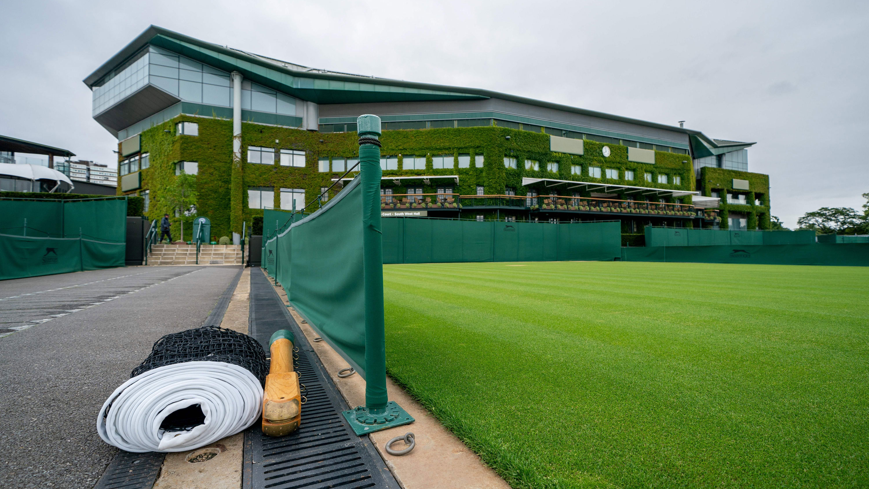 A tennis net is rolled up at the All England Lawn Tennis Club in west London on June 27, 2020.
