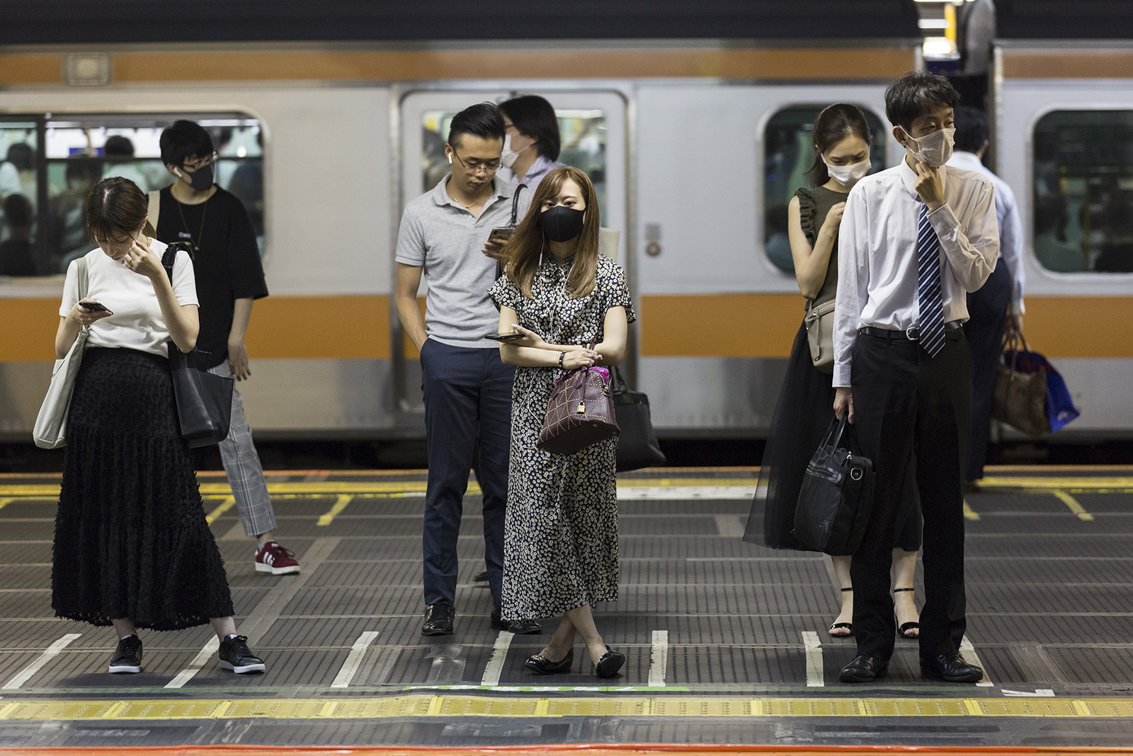 People wait for a train at Shinjuku station on August 4 in Tokyo.