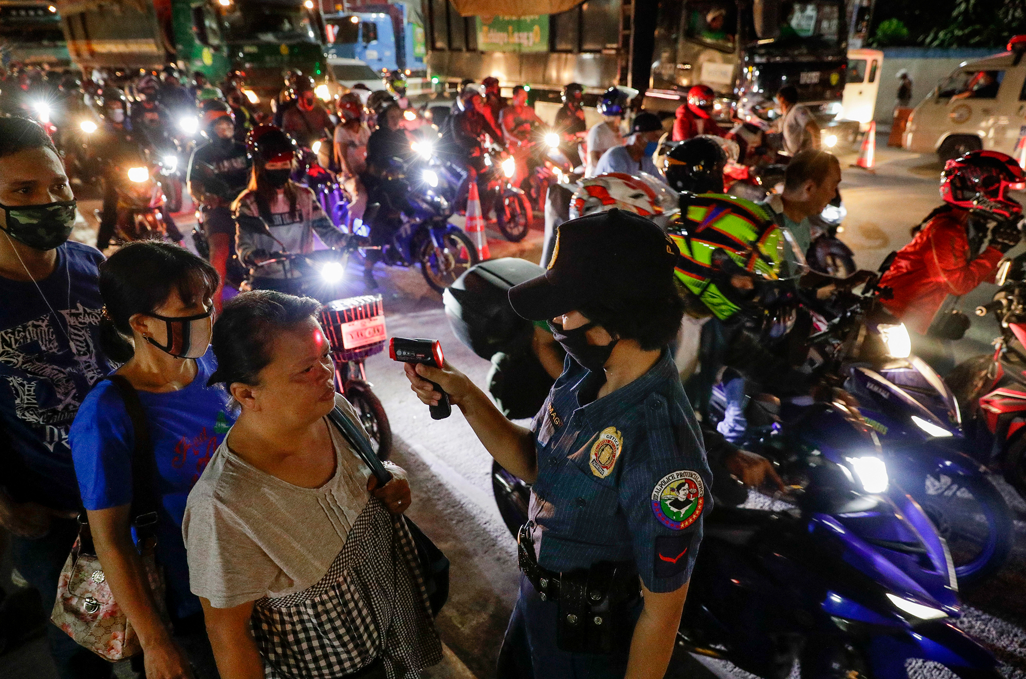 A police officer reads the temperatures of people at a checkpoint in Manila, Philippines, on March 16.