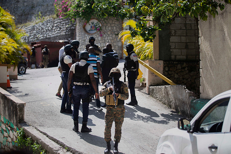 Security forces conduct an investigation as a soldier stands guard at the entrance to the residence of Haitian President Jovenel Moise, in Port-au-Prince, Haiti, Wednesday, July 7.