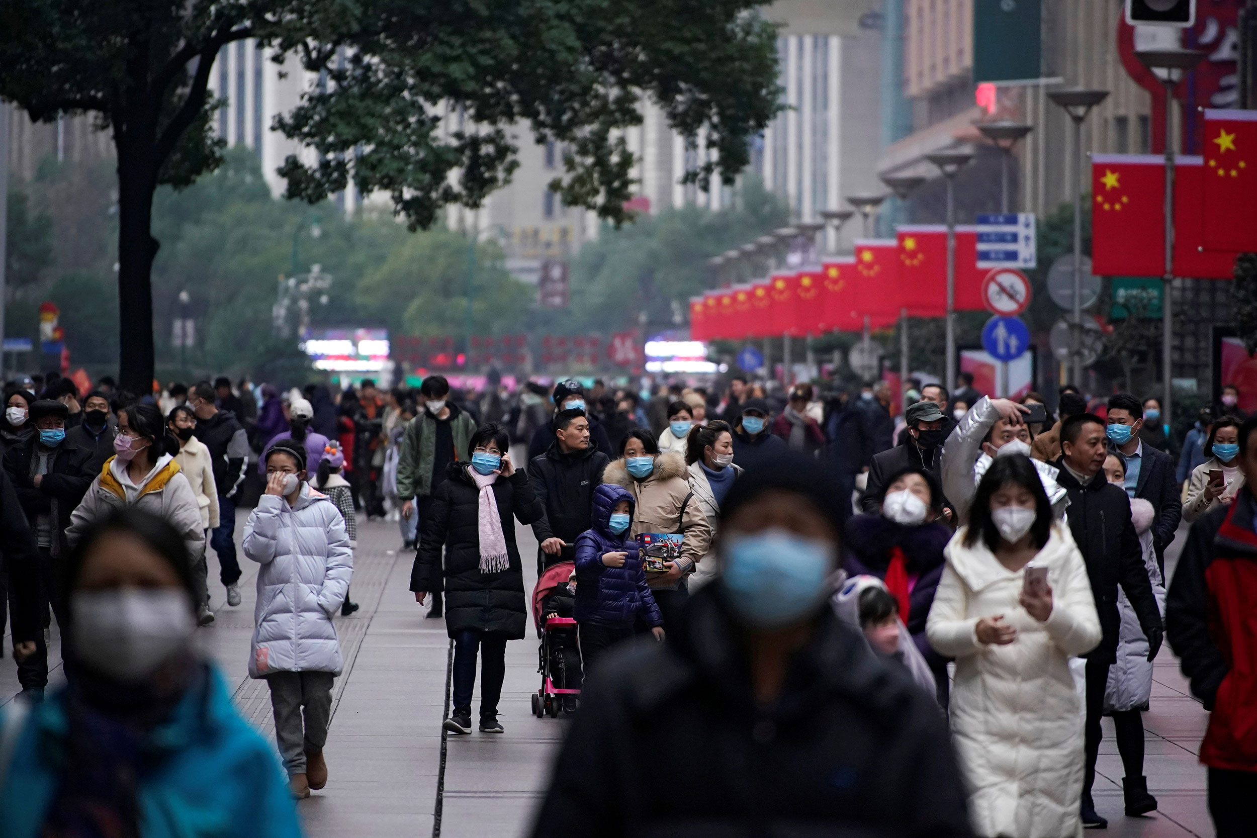 People wear masks at the Nanjing Pedestrian Road, a main shopping area, in Shanghai on Friday.