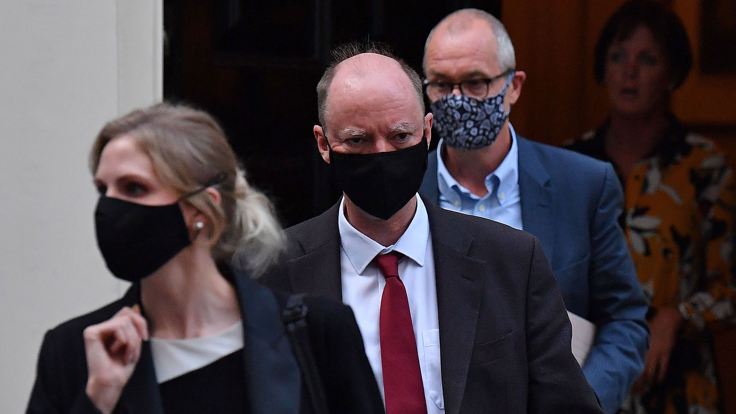 England Chief Medical Officer Chris Whitty, second from left, leaves 11 Downing Street in London on Monday.