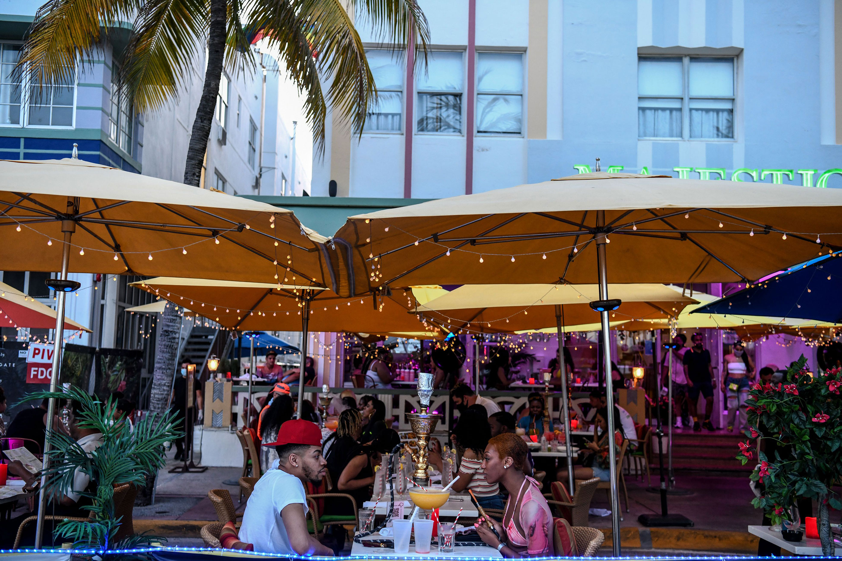 People eat outside of a restaurant on Ocean Drive in Miami Beach, Florida, on June 26.