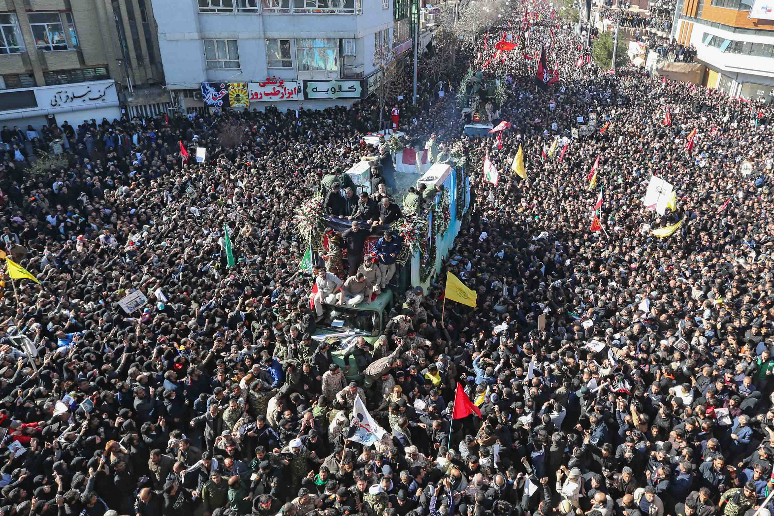 Iranian mourners gather around a vehicle carrying the coffin of Qasem Soleimani during his funeral procession in Kerman, Iran on Tuesday. Credit: Atta Kenare/AFP via Getty Images