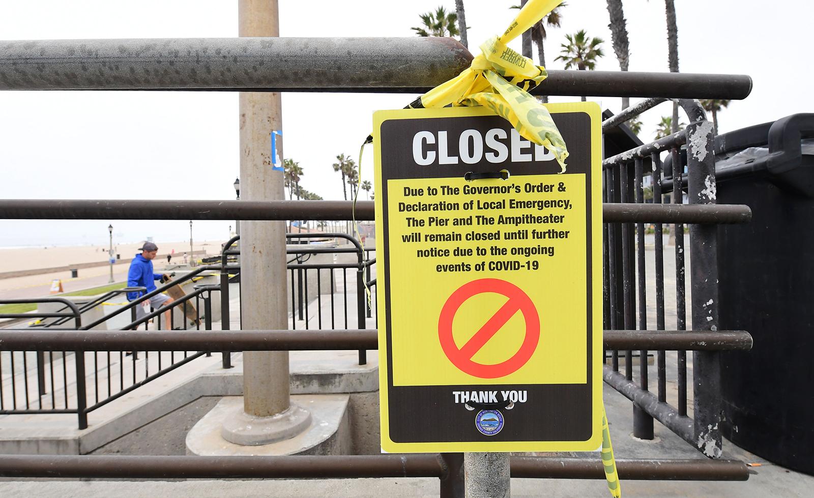 A sign announcing beach closures is seen at Huntington Beach, California, on Thursday, April 30.
