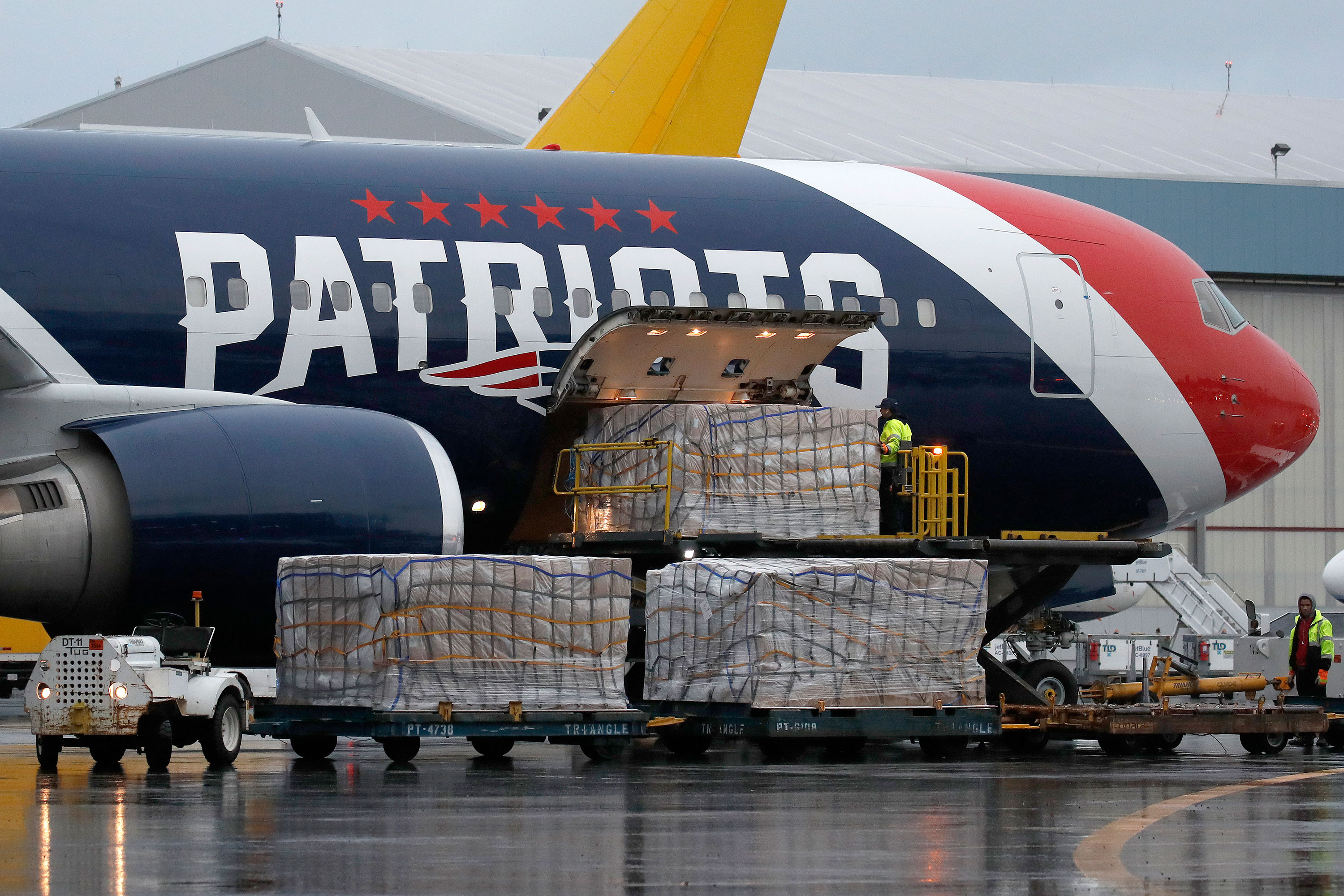 Palettes of N95 respirator masks are off-loaded from the New England Patriots football team's Boeing 767 jet on the tarmac at Logan Airport on April 2 in Boston.