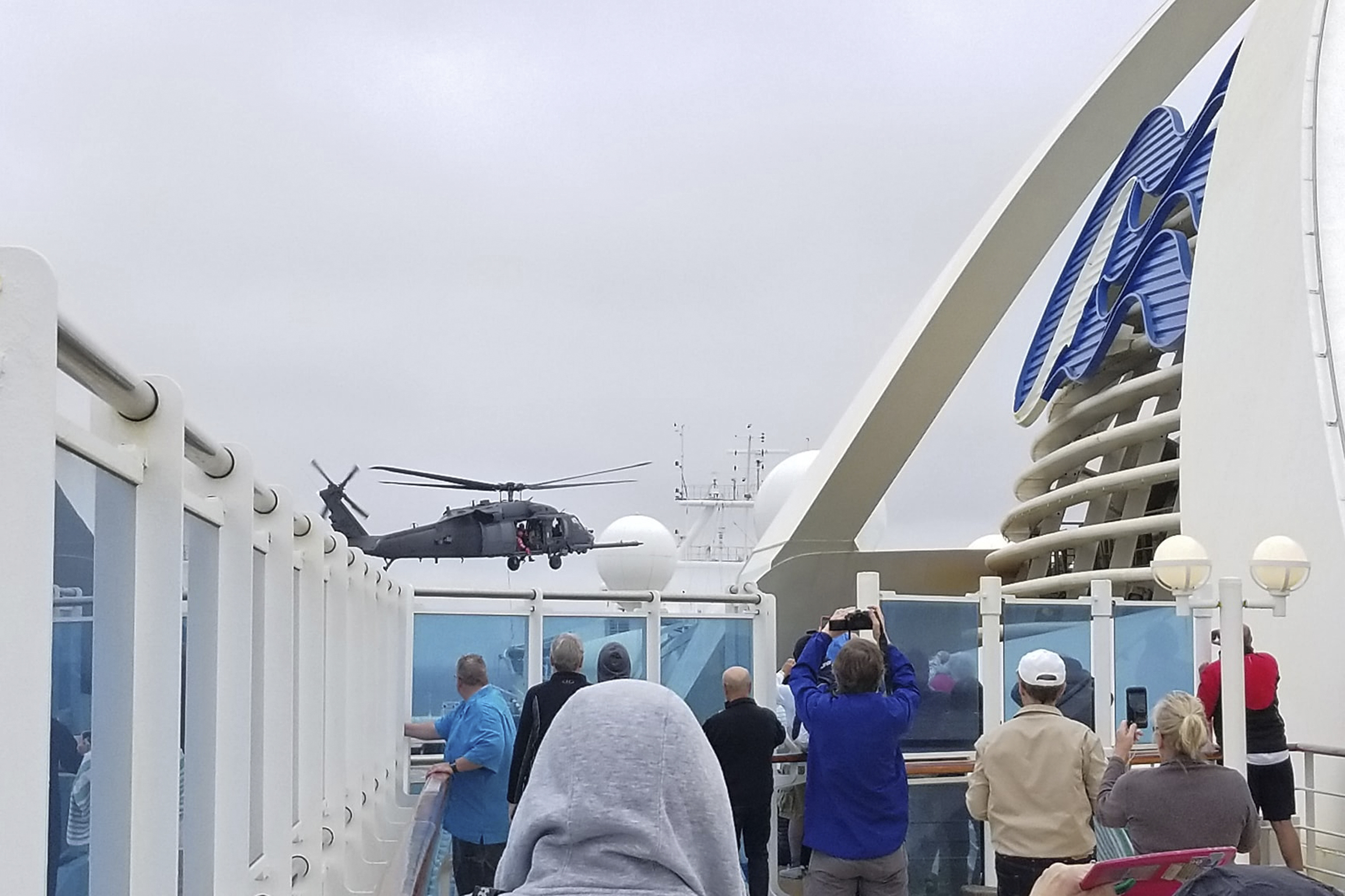 In this photo provided by Michele Smith, passengers look on as a National Guard helicopter hovers above the Grand Princess cruise ship off the California coast on Thursday.