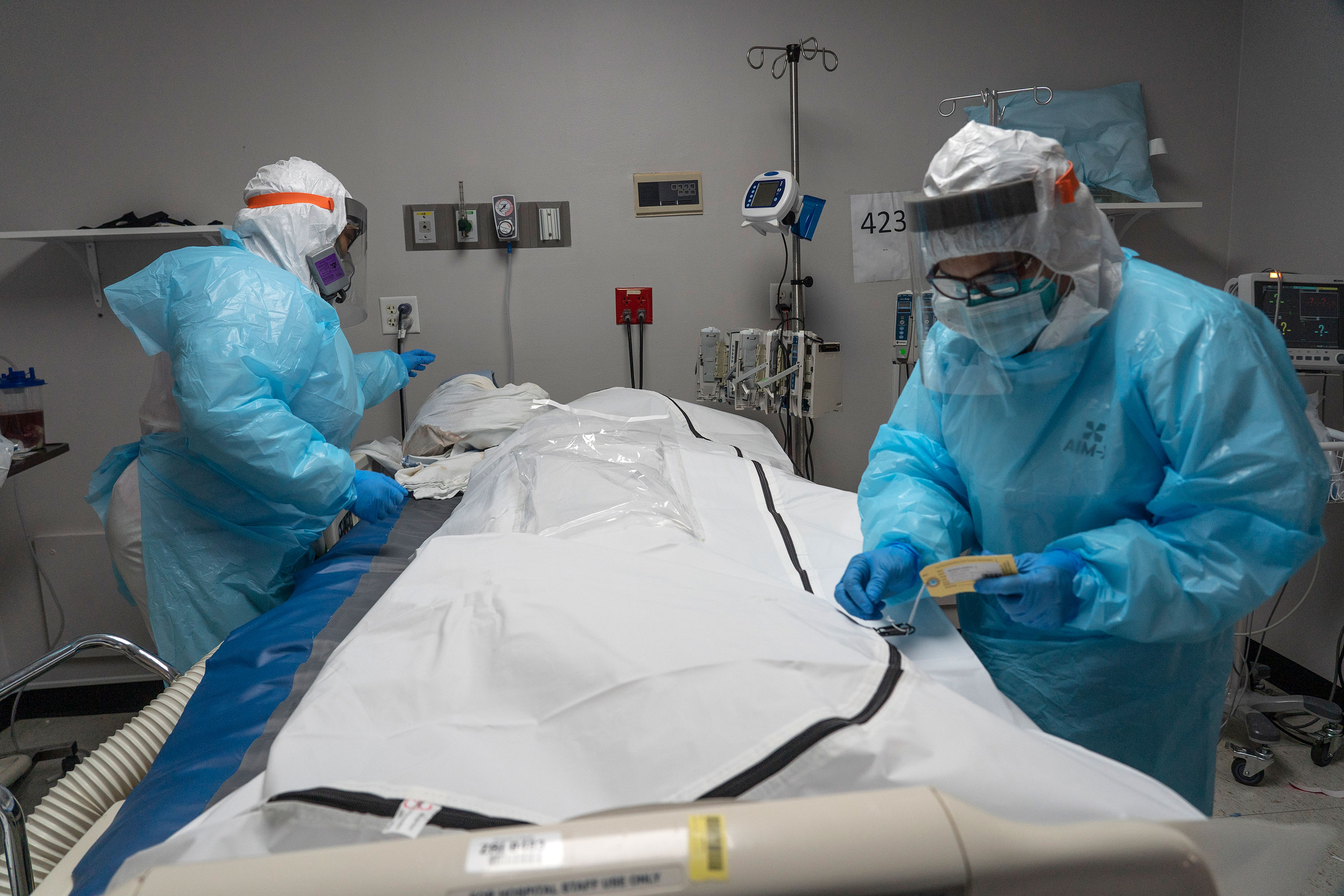 Medical staff members close the zipper of a body bag containing a deceased Covid-19 patient in the intensive care unit of United Memorial Medical Center on November 25 in Houston, Texas.