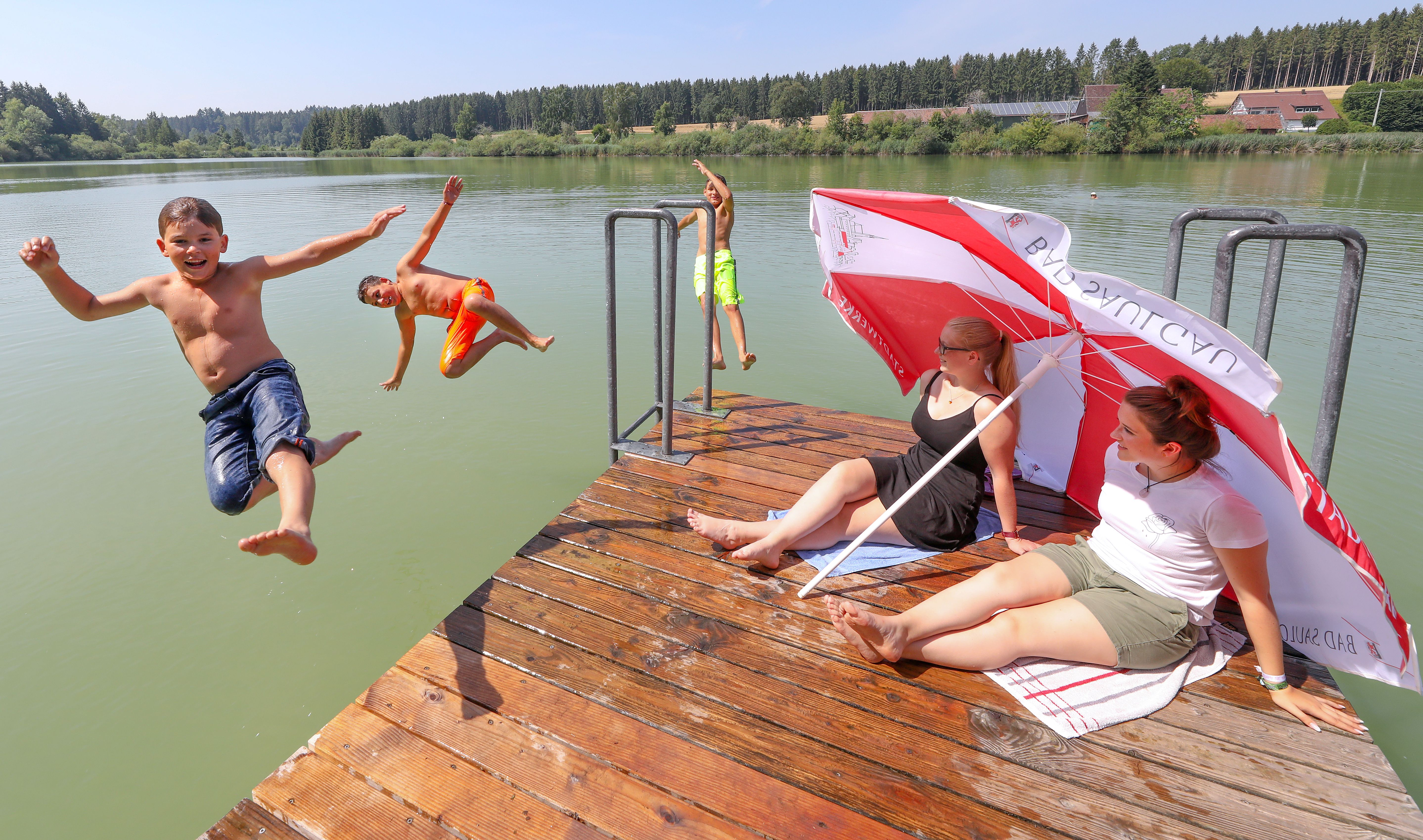 Two women sitting under parasols watch three boys jumping into a lake in Bad Saulgau, Germany on July 25, 2019.