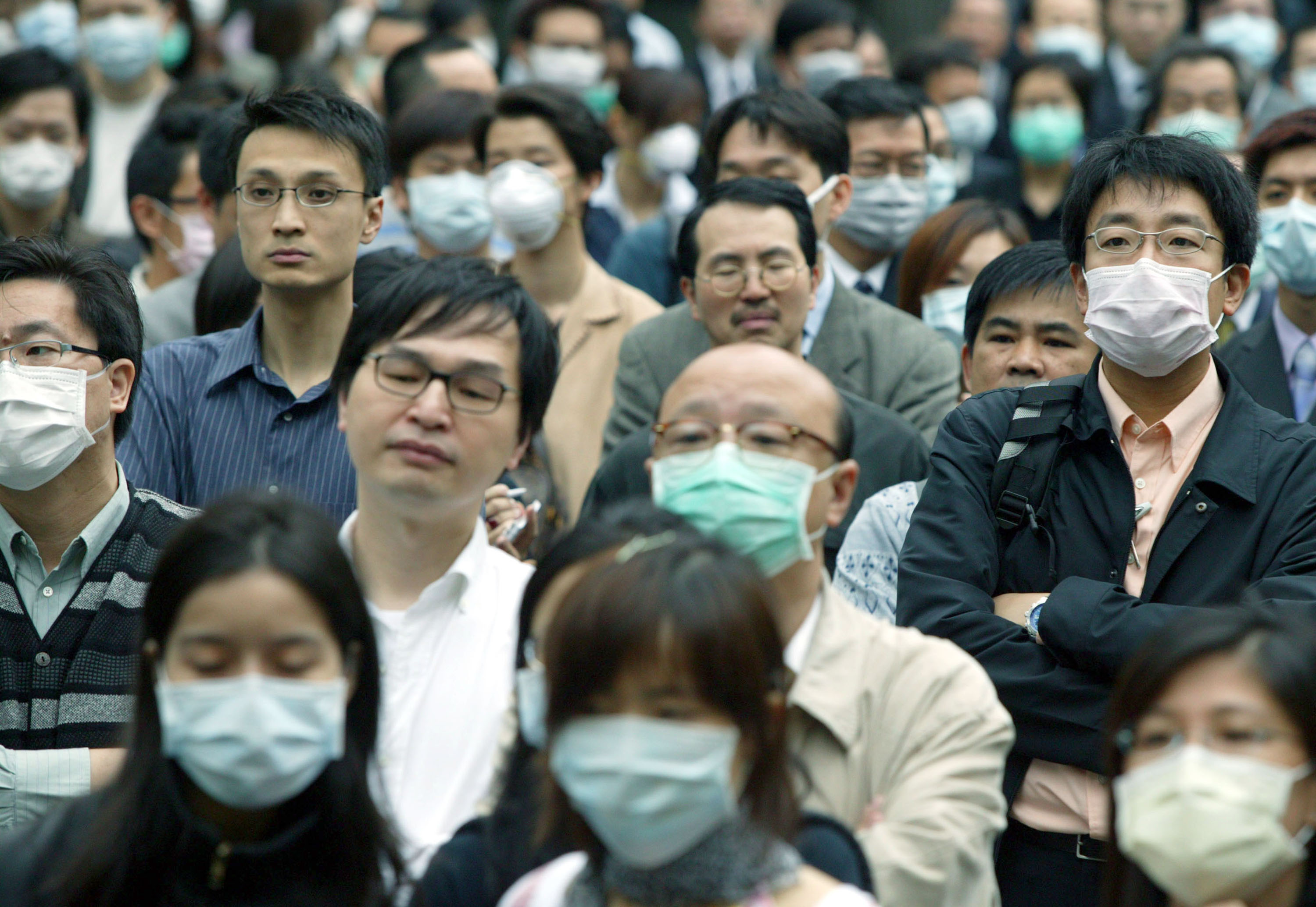 People wear masks to protect themselves against the Severe Acute Respiratory Syndrome (SARS) virus April 16, 2003 in Hong Kong. Christian Keenan/Getty Images