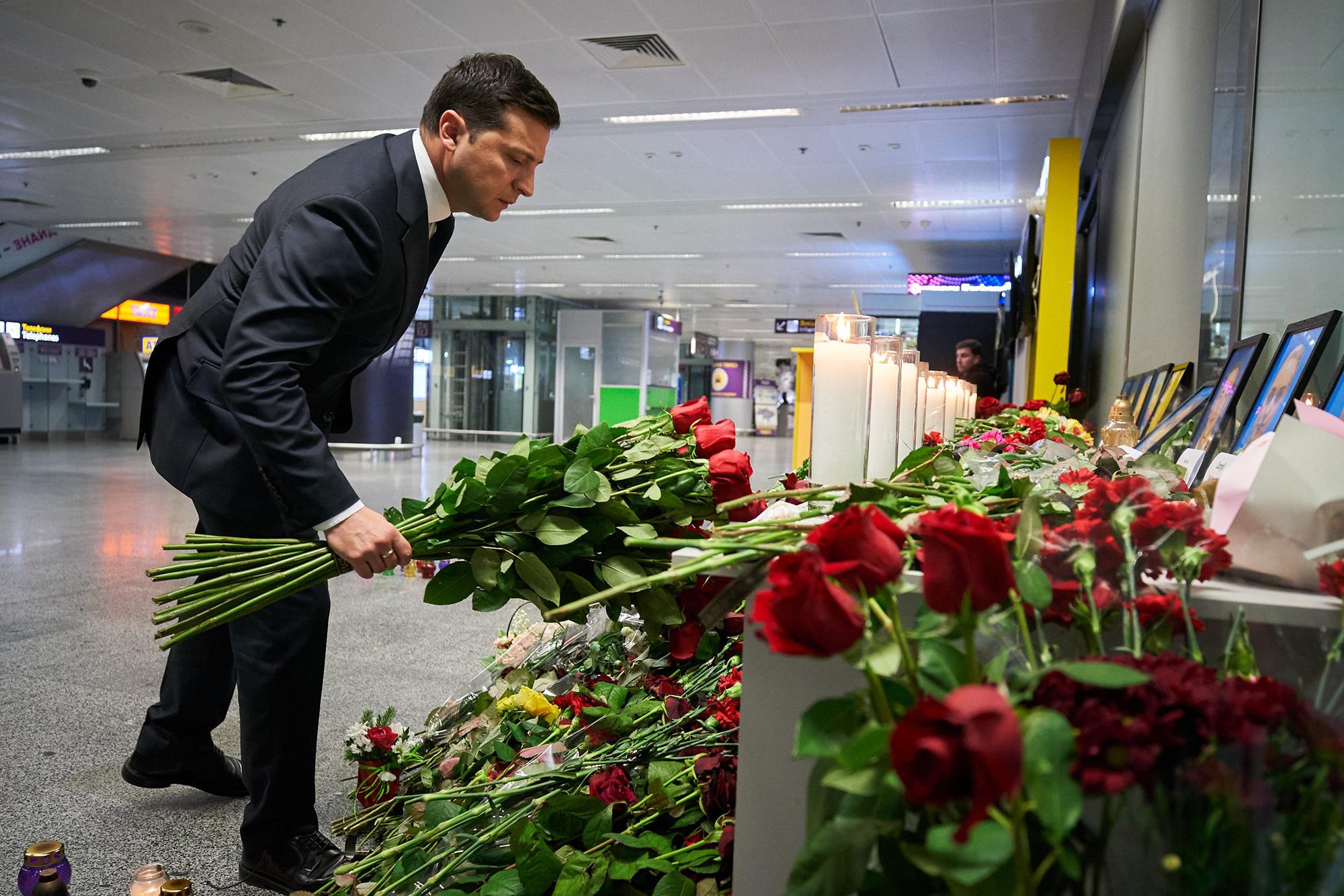 Ukrainian President Volodymyr Zelensky places flowers near the photographs of the dead at Ukraine's Boryspil airport.