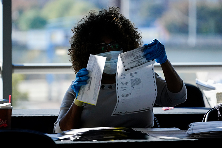An election personnel examines a ballot as vote counting in the general election continues at State Farm Arena, Wednesday, November 4, in Atlanta.