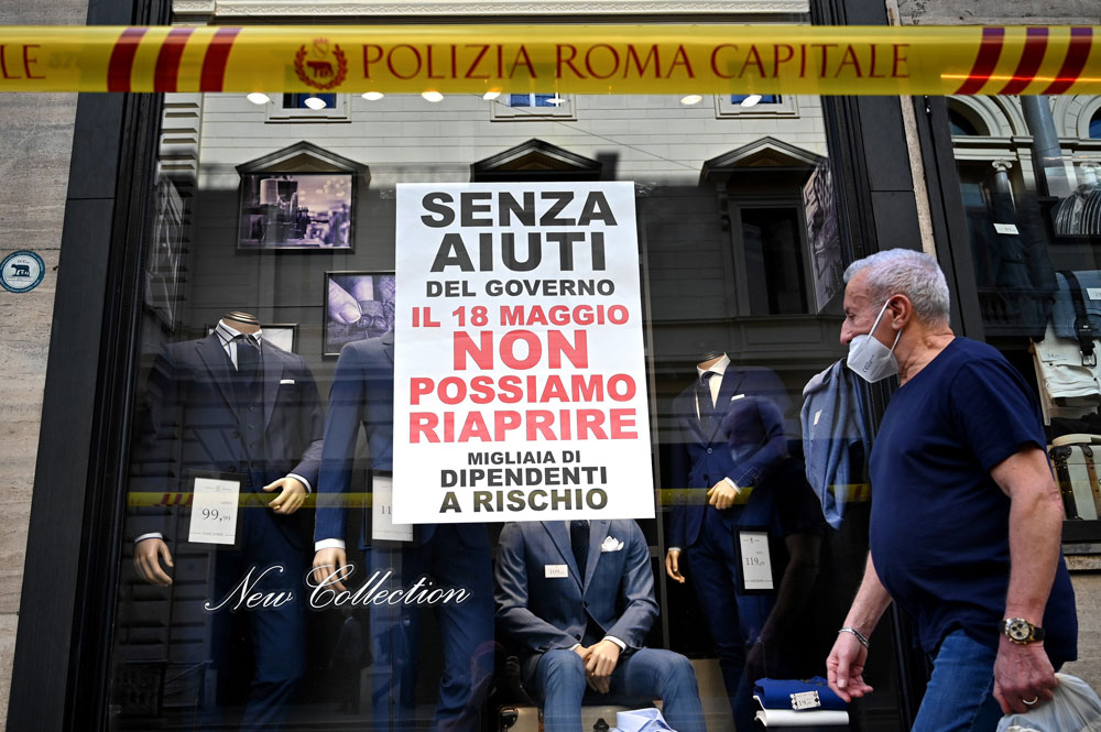 """A banner reading """"Without government aid, we cannot reopen on May 18. Thousands of employees at risk"""" is seen at a shop window on Tuesday in Rome."""