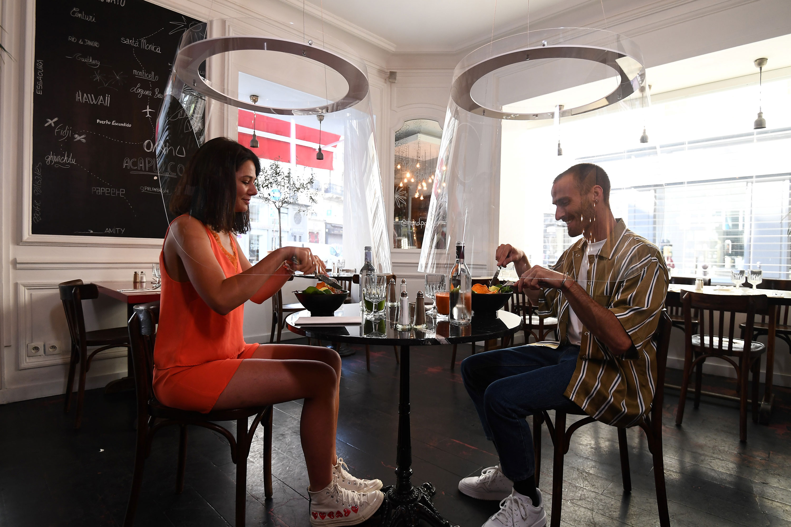 A couple has lunch under plexiglass in Paris on May 27.