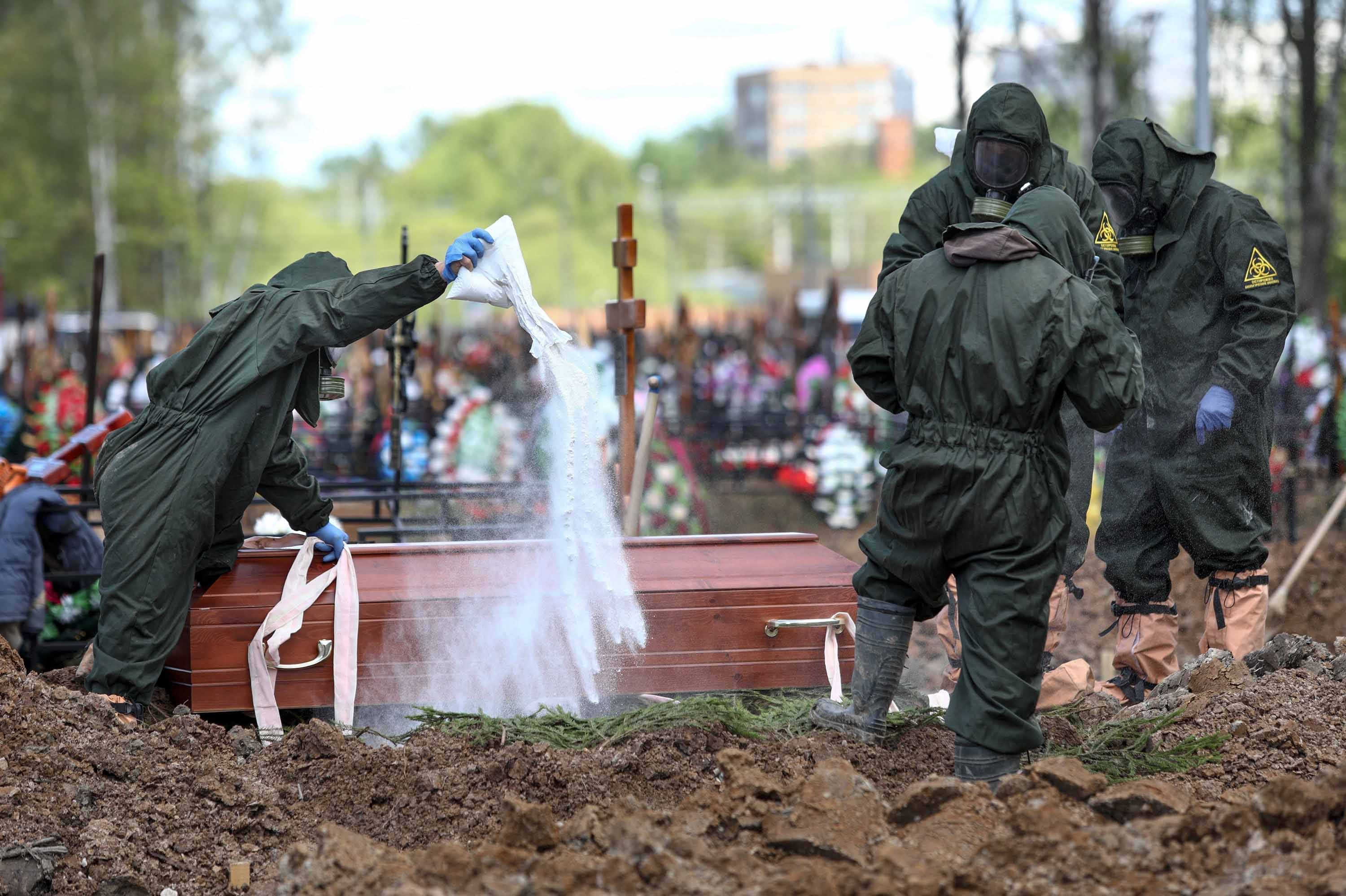 Cemetery workers disinfect a grave as they bury a COVID-19 victim in the Butovskoye cemetery outside Moscow, Russia on May 15, 2020.
