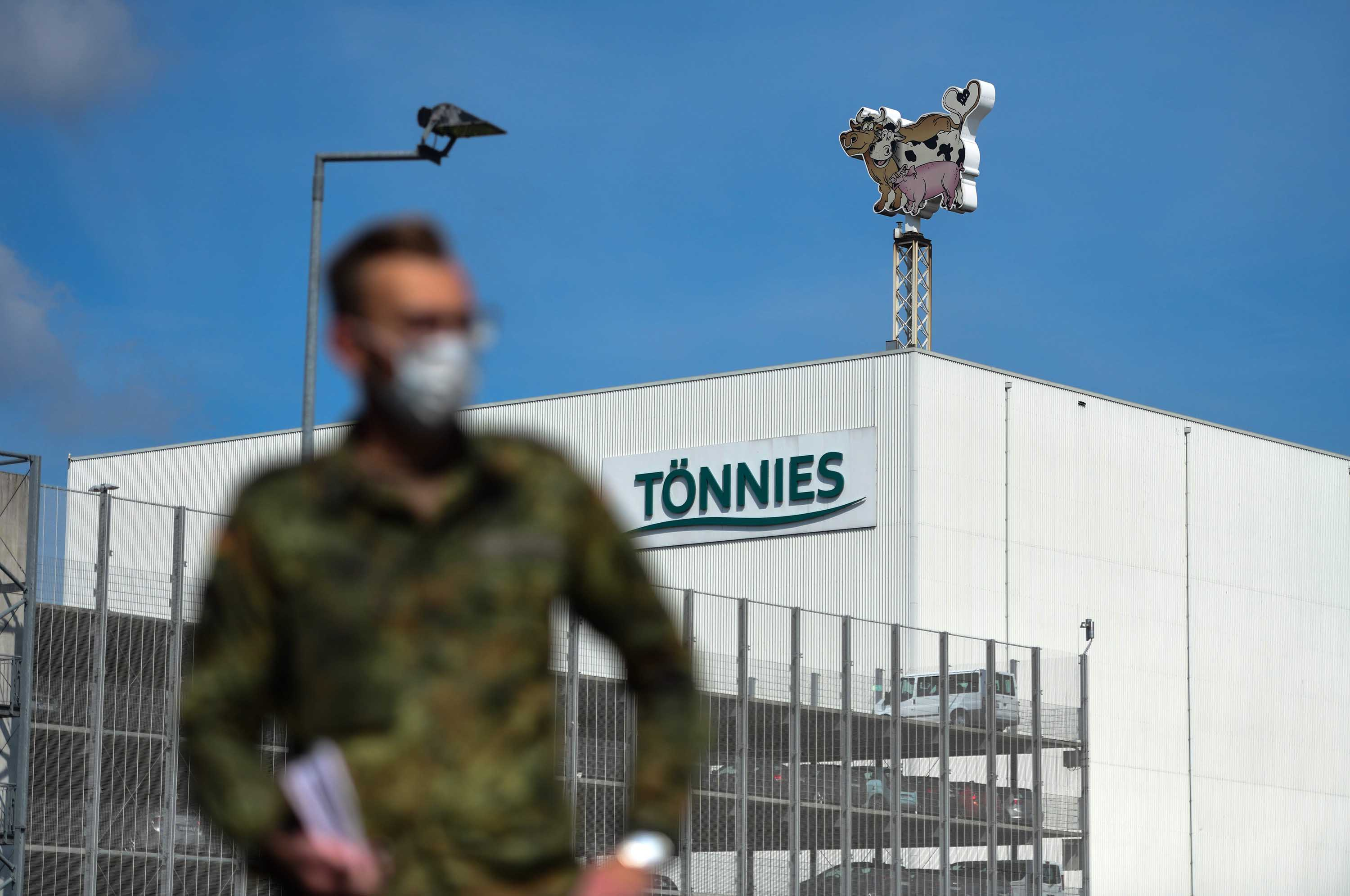 A soldier of the German armed forces stands outside the headquarters of abattoir company Toennies, in Rheda-Wiedenbrueck, western Germany, on June 19, amid a coronavirus outbreak at the plant.