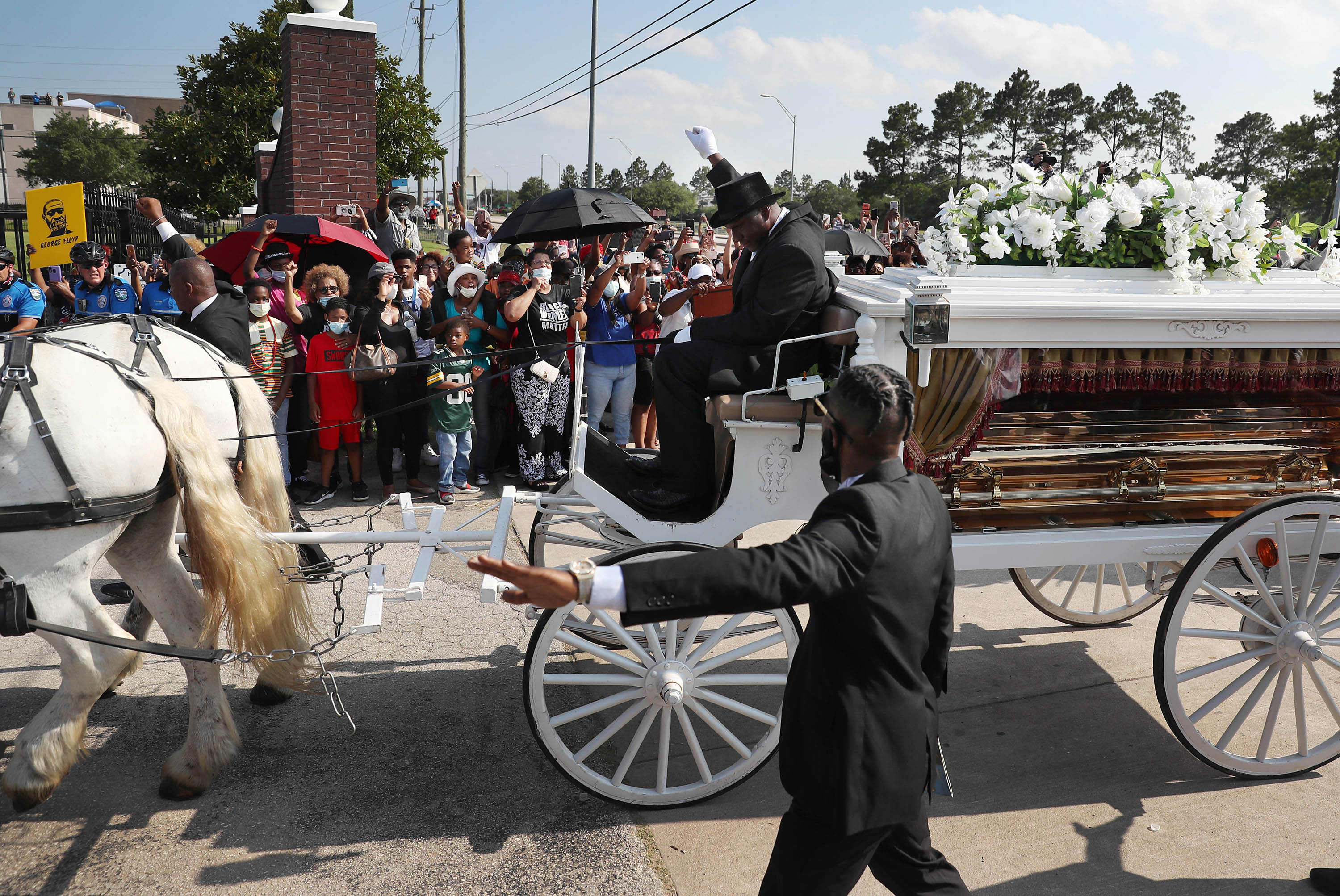 Terence Reed Jr. raises his arm as he drives his horse drawn hearse containing the remains of George Floyd into the Houston Memorial Gardens cemetery in Houston on June 9.