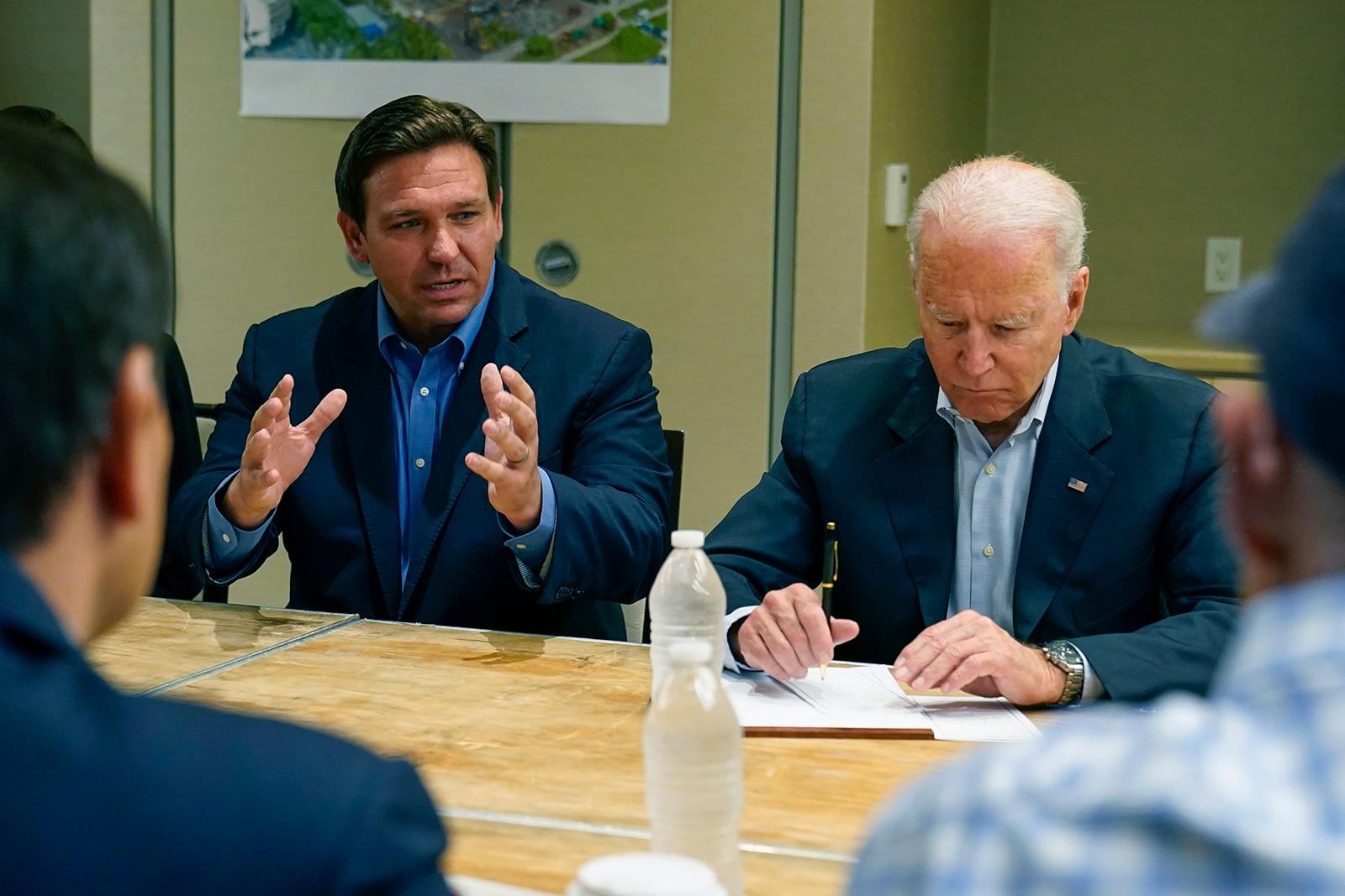 President Joe Biden listens as Florida Gov. Ron DeSantis speaks during a briefing in Miami Beach, Florida, on Thursday, July 1.