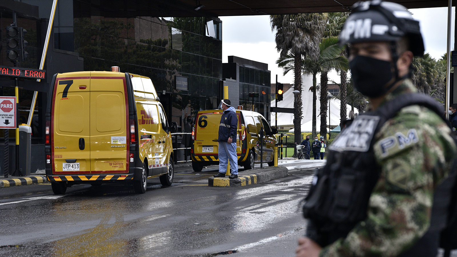 A soldier stands guard as DHL company vans transport a batch of doses of the Pfizer-BioNTech Covid-19 vaccine to the Free Trade Zone to be stored in freezers on February 15, in Bogota, Colombia.