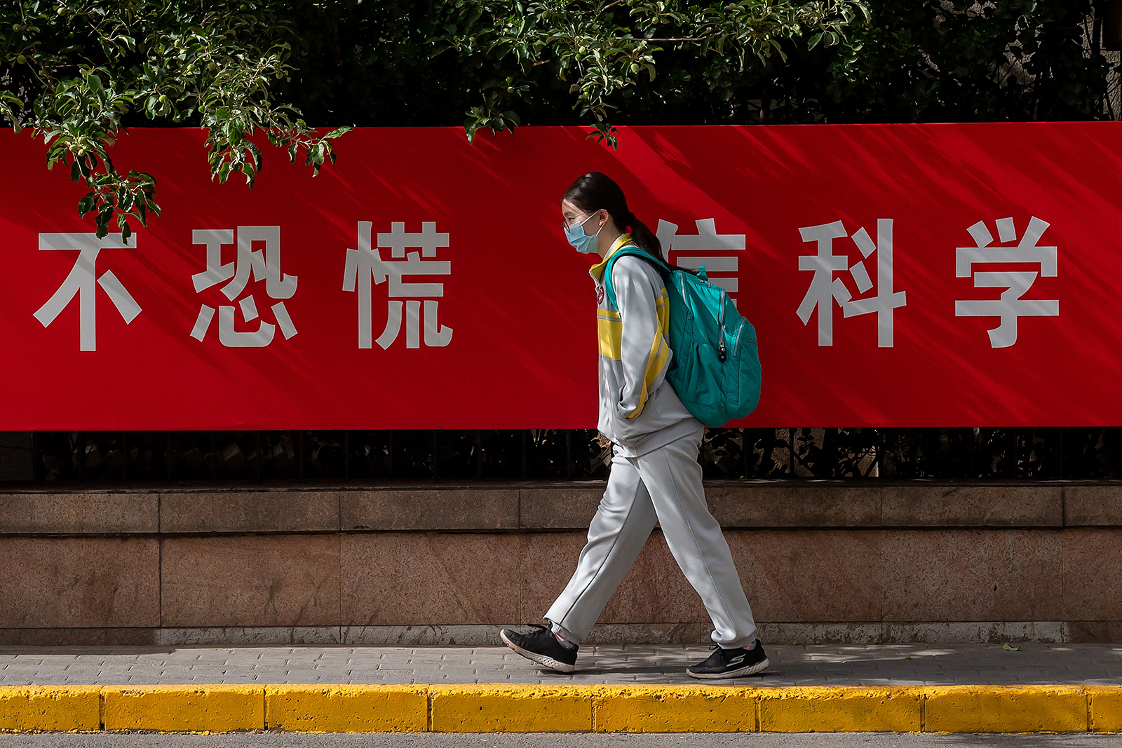 "A student wearing a face mask amid concerns of the coronavirus passes by a propaganda poster on a street that reads ""No Panic Trust Science"" as she leaves a middle school in Beijing on May 11."
