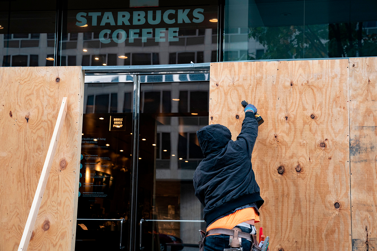 Wooden boards protect a Starbucks location near the White House on October 31, in Washington, DC.