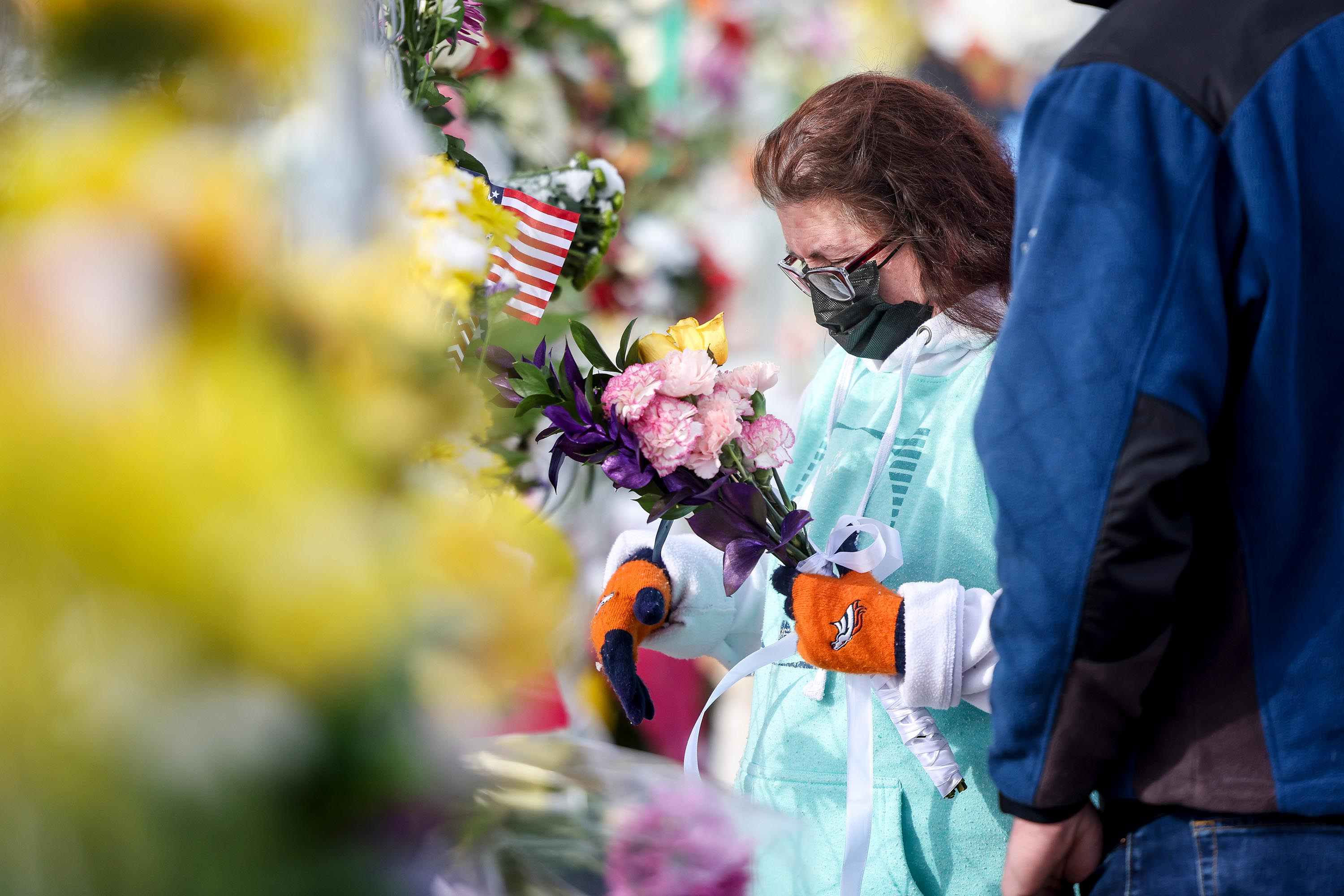 Mourners place flowers at a makeshift memorial for the victims of the attack outside the King Soopers grocery store on March 24, 2021 in Boulder, Colorado.