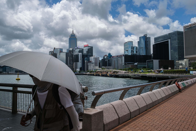 Pedestrians pass a view of the Hong Kong skyline on July 16.