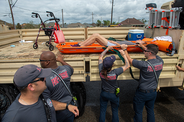 St. John the Baptist Parish rescue teams place a person onto the back of a truck during an evacuation on the morning after Hurricane Ida hit the area, Monday, August 30, in St. John the Baptist Parish, Louisiana.