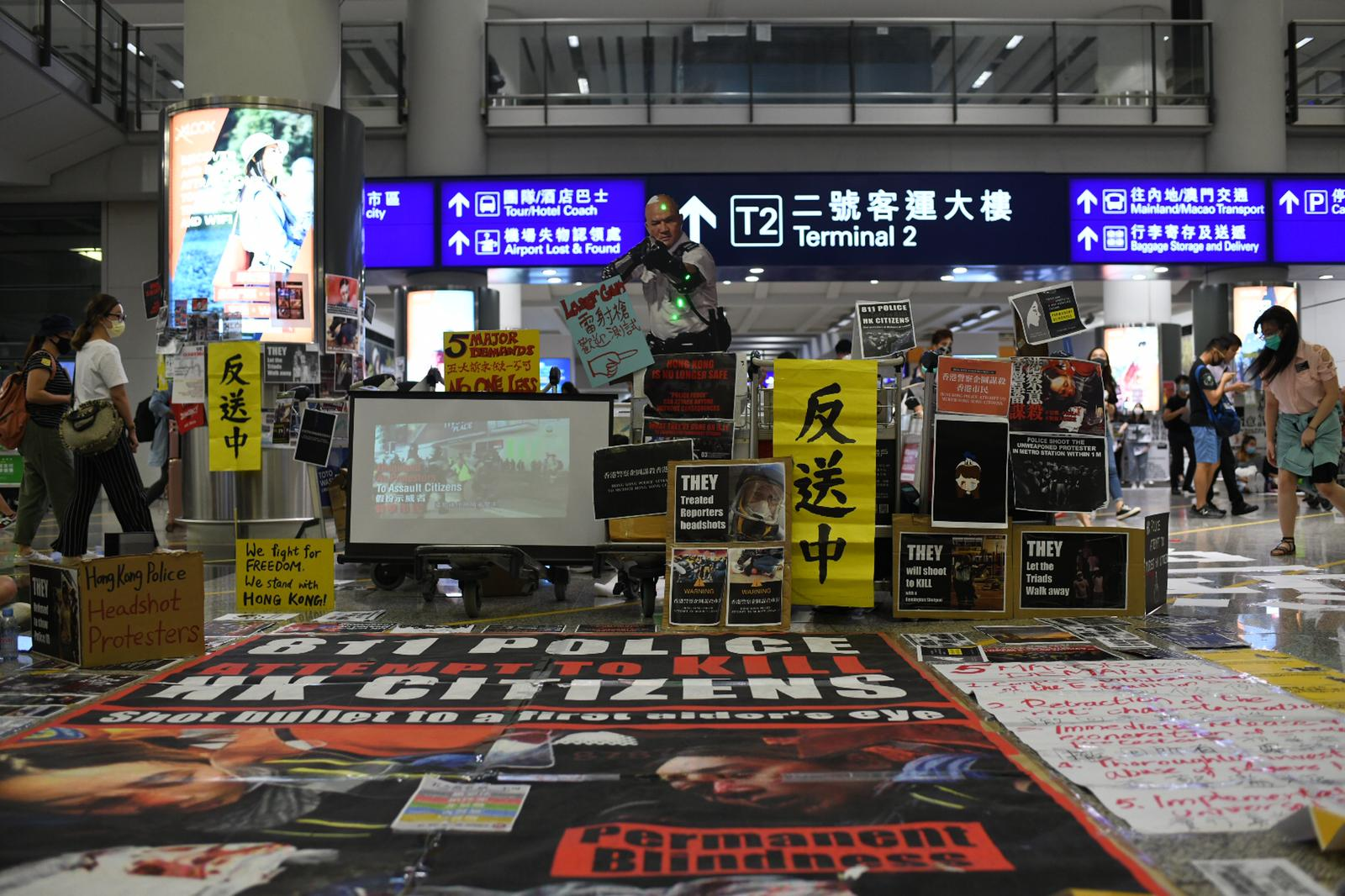 Posters and signs adorn the Hong Kong airport terminal as protesters shut down the airport for a second day.