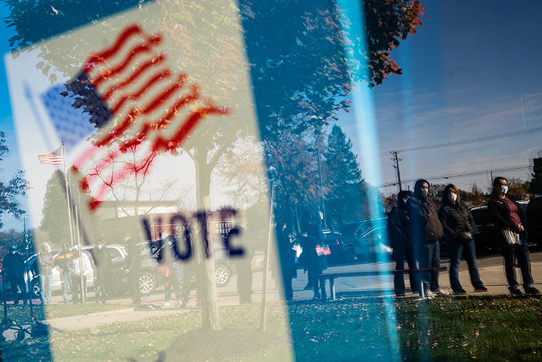 People wait in line to casts their absentee ballots in person at the Sterling Heights Election Center located in the Senior Center in Sterling Heights, Michigan on Monday, Nov. 2, 2020.