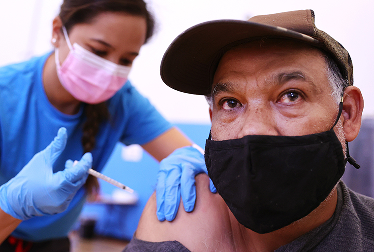 A nurse administers a vaccine dose to a person at a vaccination clinic at Providence Wilmington Wellness and Activity Center on July 29, 2021 in Wilmington, California.
