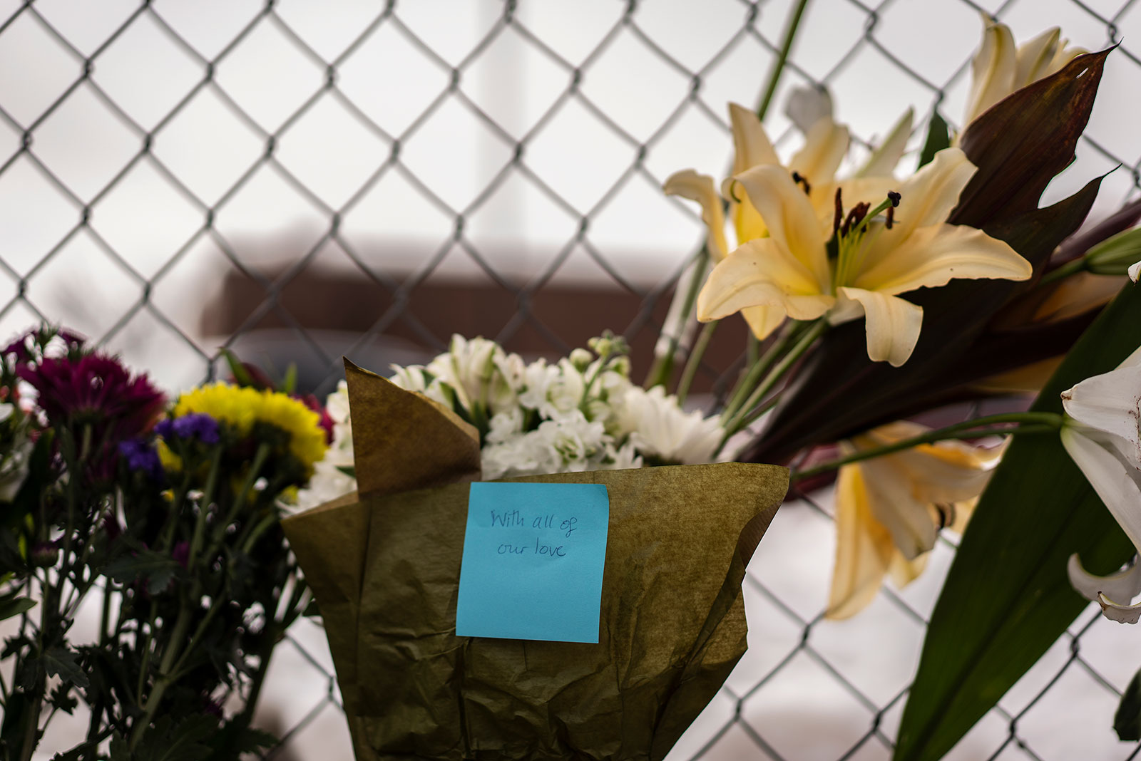 "A note left on a bouquet of flowers reads ""with all of our love."""