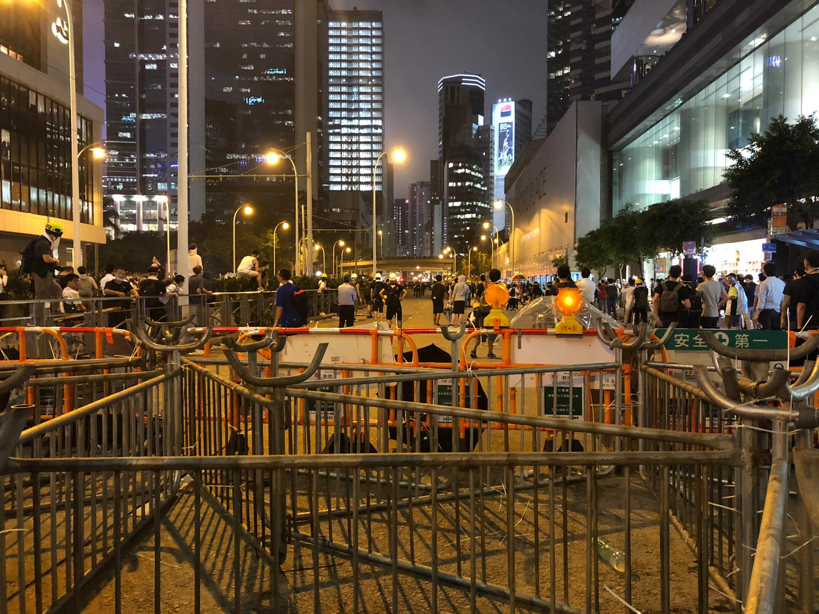 Barricades by Pacific Place where crowds of protesters are gathered.