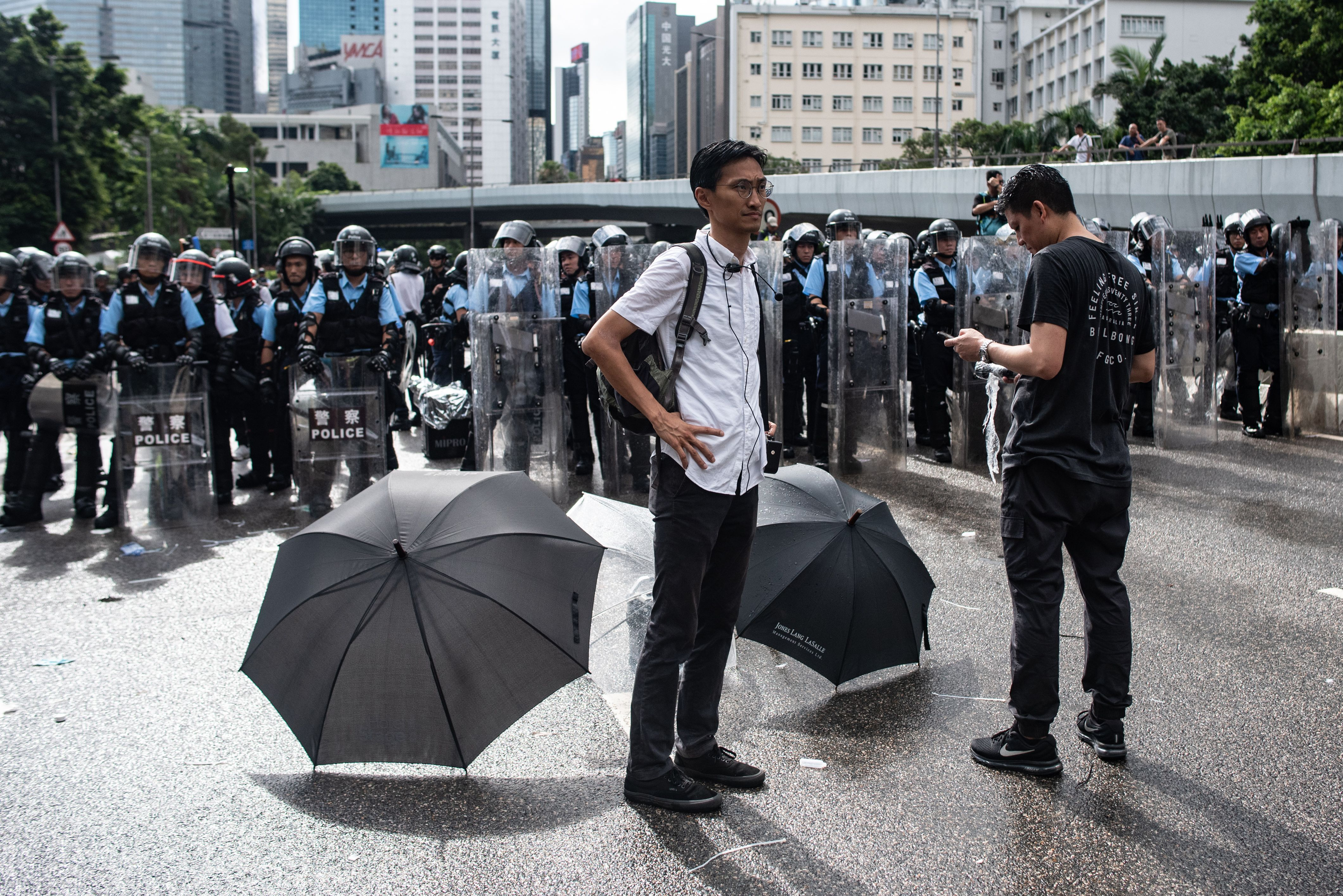 Pro-democracy lawmaker Eddie Chu (L) and Jeremy Tam (R) stand before a police line on Harcourt Road outside the government headquarters after the annual flag raising ceremony to mark the 22nd anniversary of the city's handover from Britain to China, in Hong Kong on July 1.