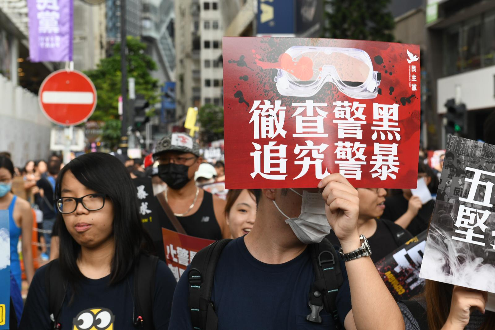 Protesters hold signs as part of a pro-democracy march in Victoria Park on August 18, 2019.