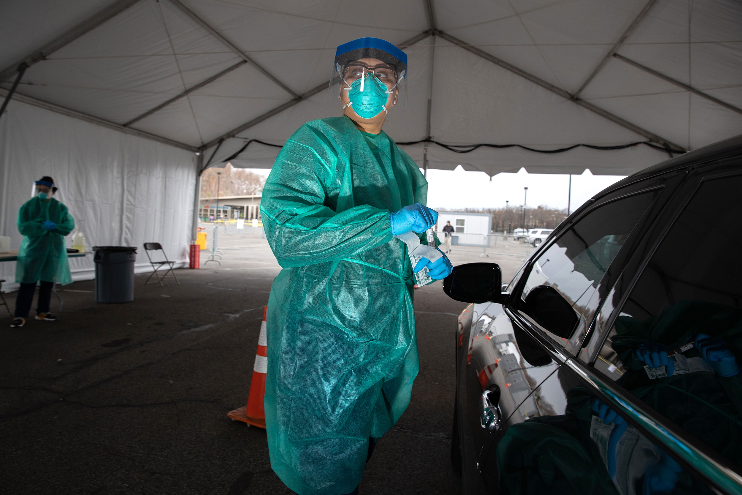 A doctor from SOMOS Community Care prepares to test a patient at a drive-through testing center at Lehman College in New York City on March 28.