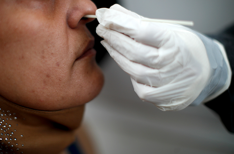 A healthcare worker conducts a nasal swab test for COVID-19 from inside a freestanding coronavirus testing isolation booth at a hospital in Buenos Aires, Argentina, Monday, October 19.