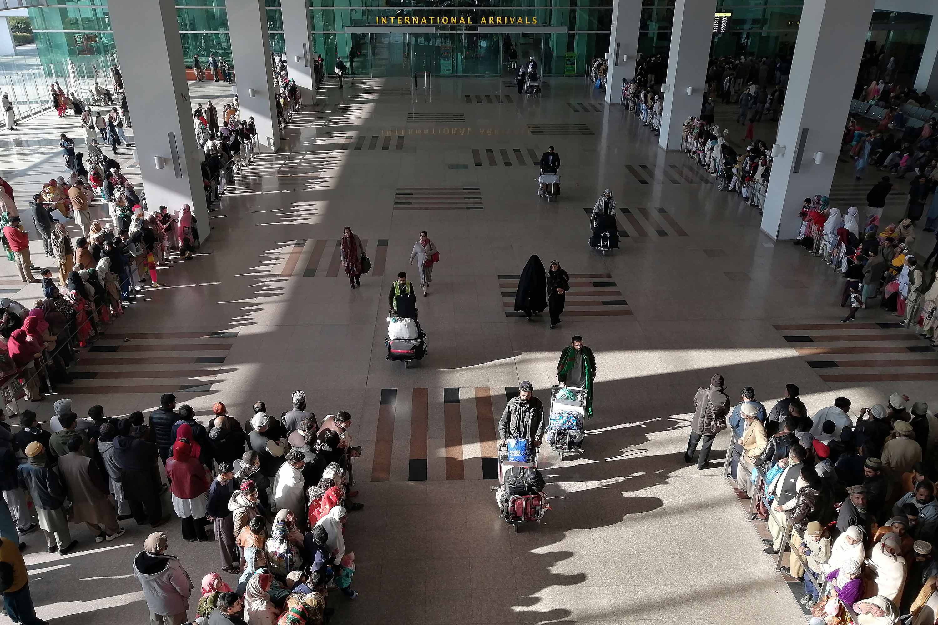 People gather to receive arriving passengers at the Islamabad International Airport in Pakistan on Monday.