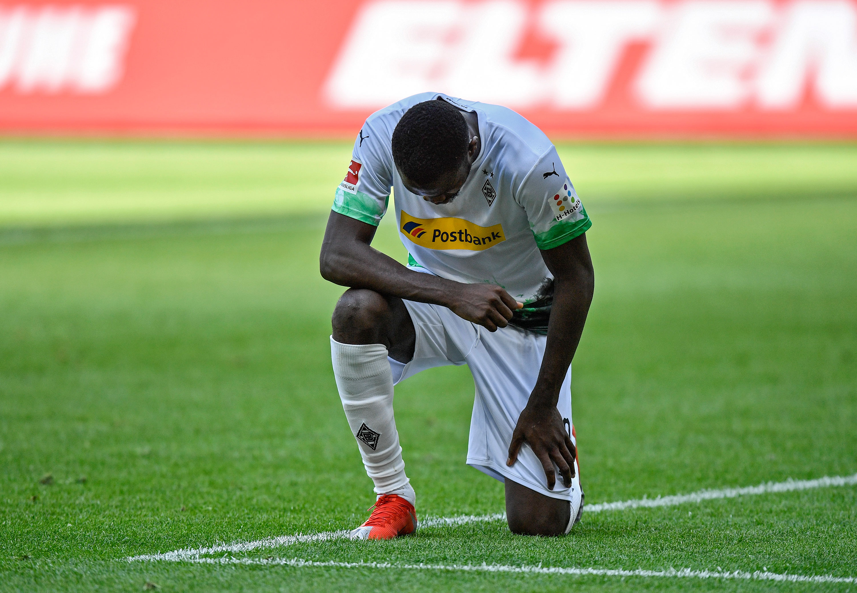 Borussia Möchengladbach forward Marcus Thuram takes a knee after scoring in the match between Möchengladbach and Union Berlin in Mönchengladbach, Germany, on May 31.