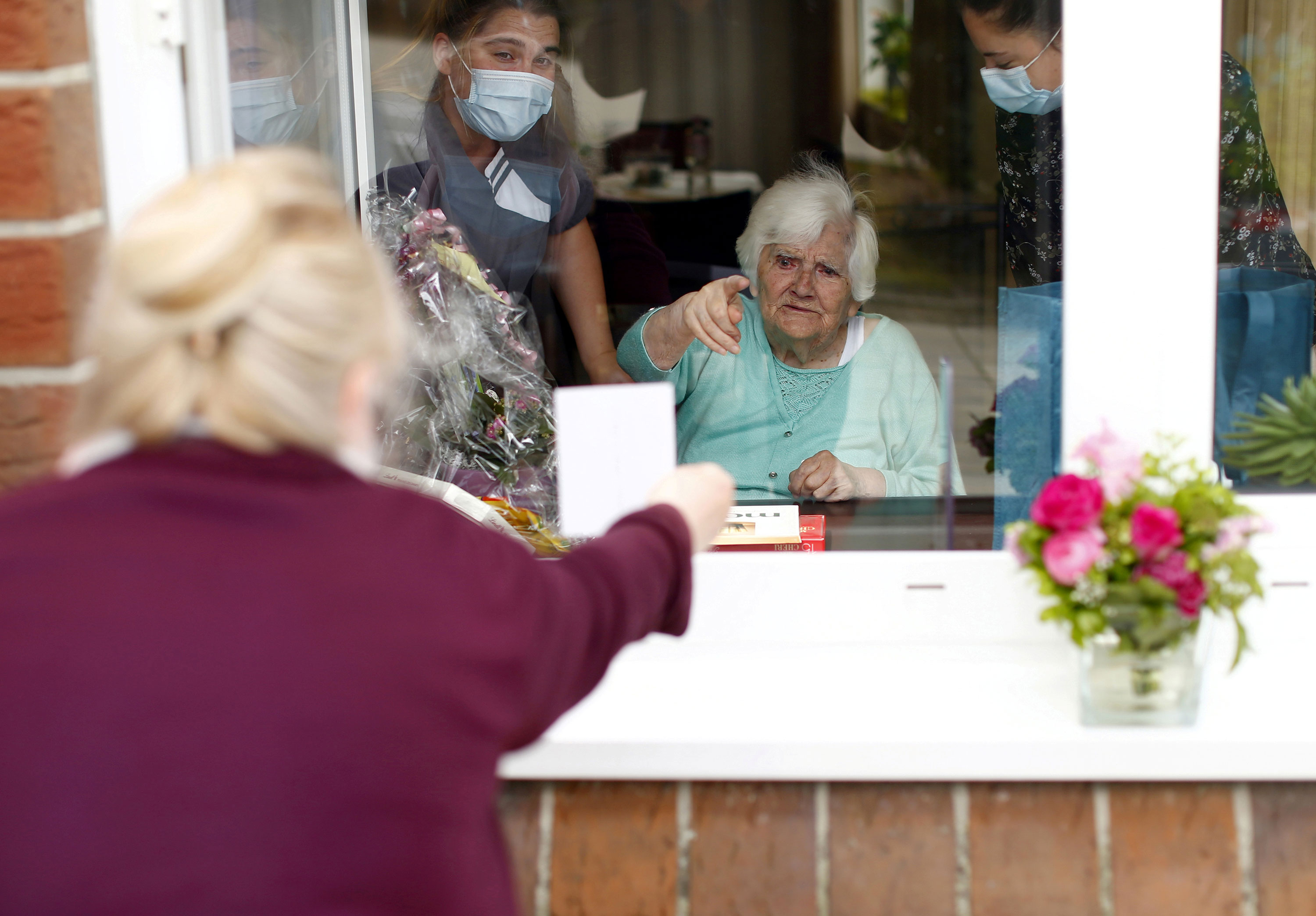 A woman shows family pictures to her mother through a window in Neuss, Germany, on Mother's Day, May 10.