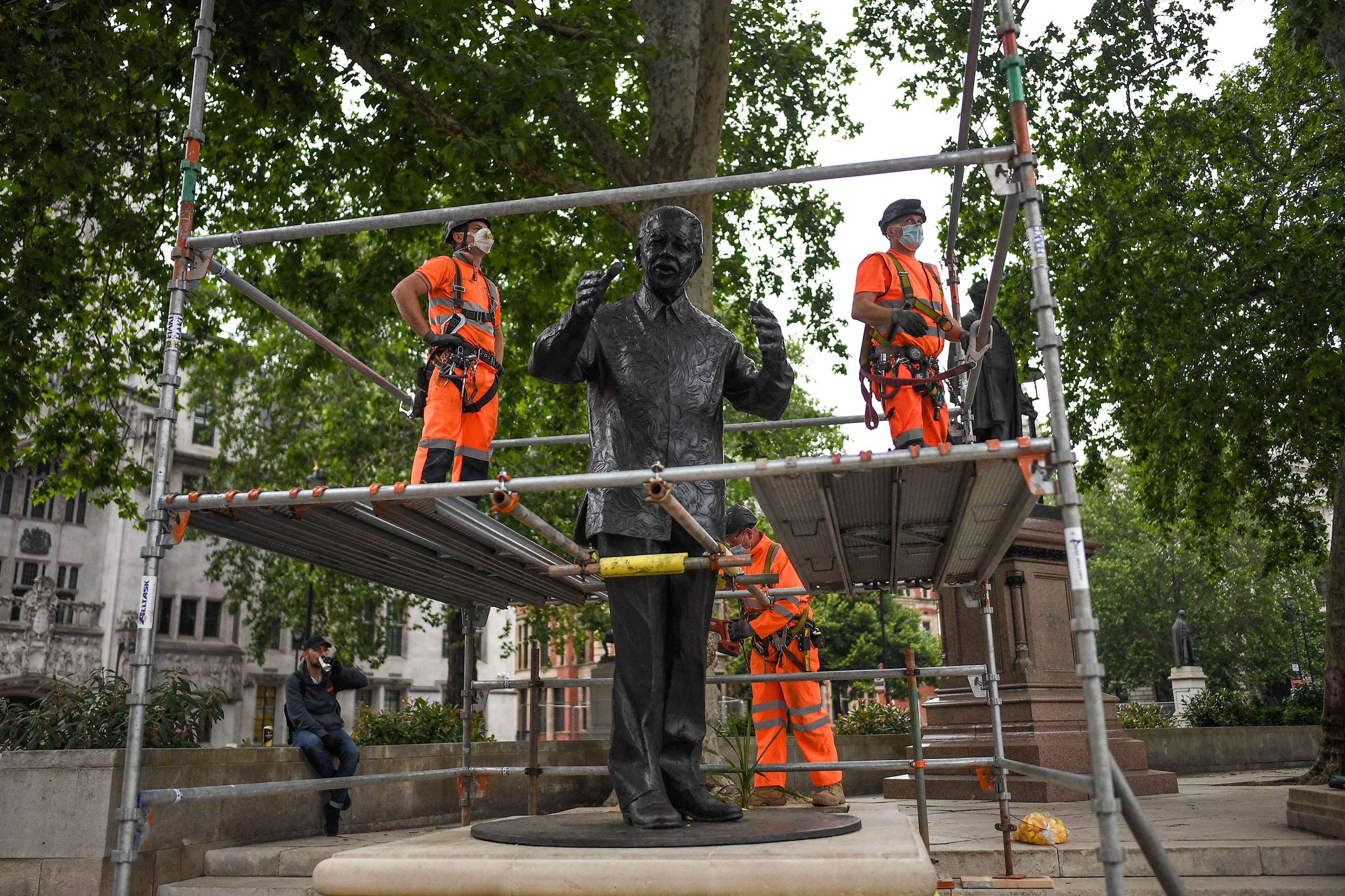 Workers build a protective barrier around the statue of Nelson Mandela in Parliament Square on June 12 in anticipation of protests on Saturday in London.