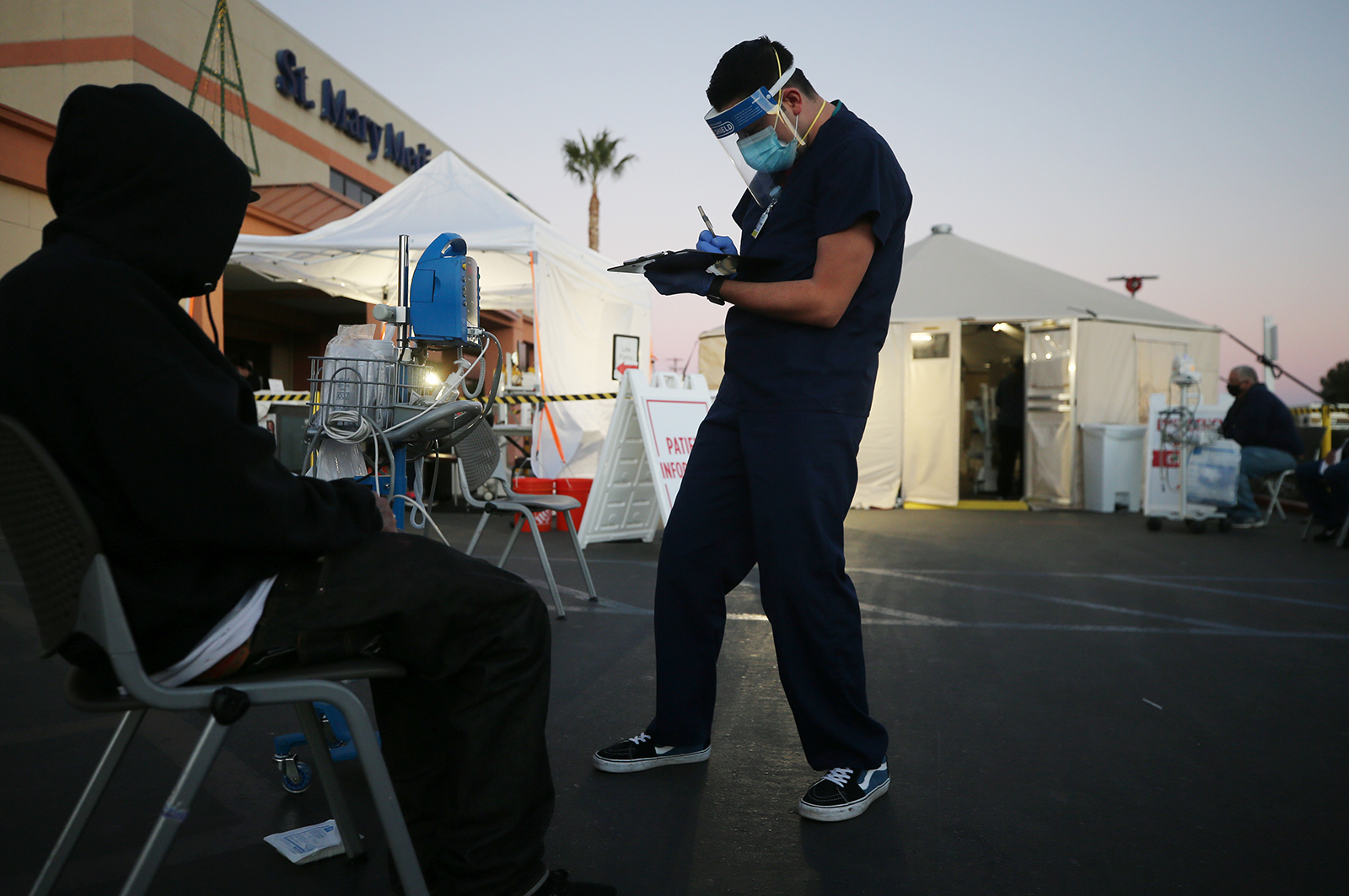 A California National Guard medic checks the vital signs of an incoming patient in front of triage tents set up outside Providence St Mary Medical Center amid a surge in Covid-19 patients in Southern California on December 18, in Apple Valley, California.