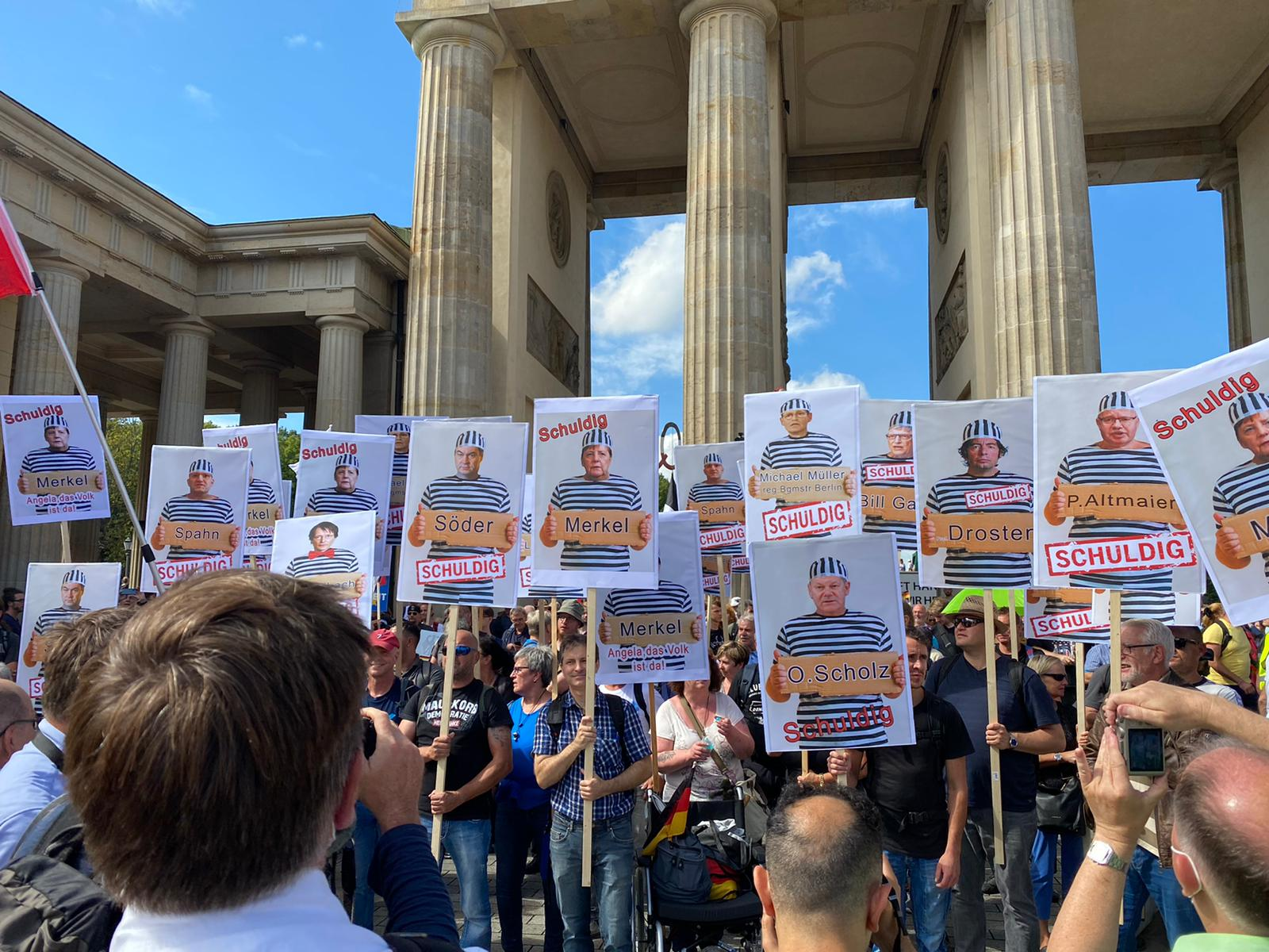 """Protesters in Berlin hold up placards featuring pictures of German lawmakers and the word """"Guilty."""""""