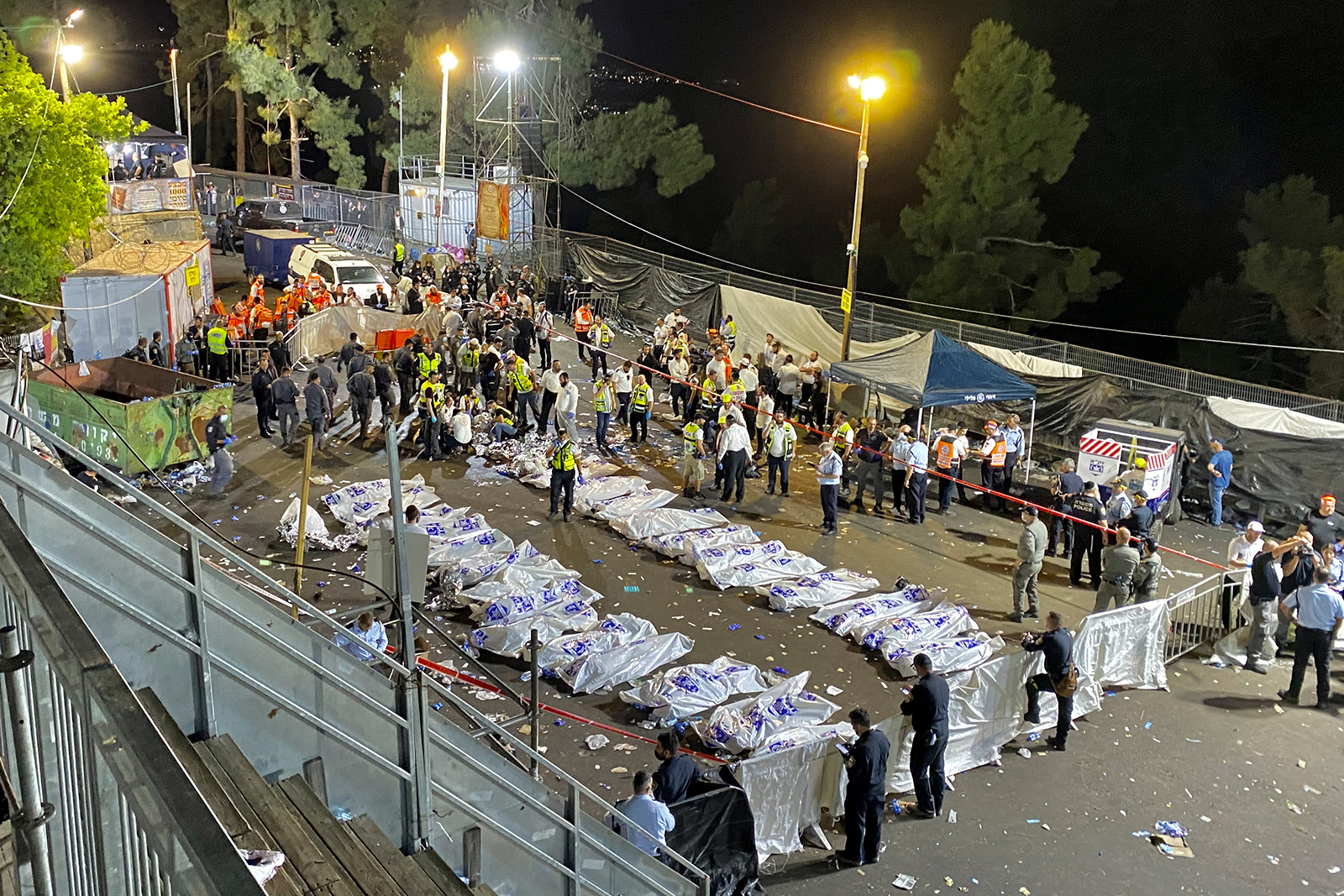 Israeli security officials and rescuers stand around the bodies of victims who died during Lag Ba'Omer celebrations at Mount Meron.