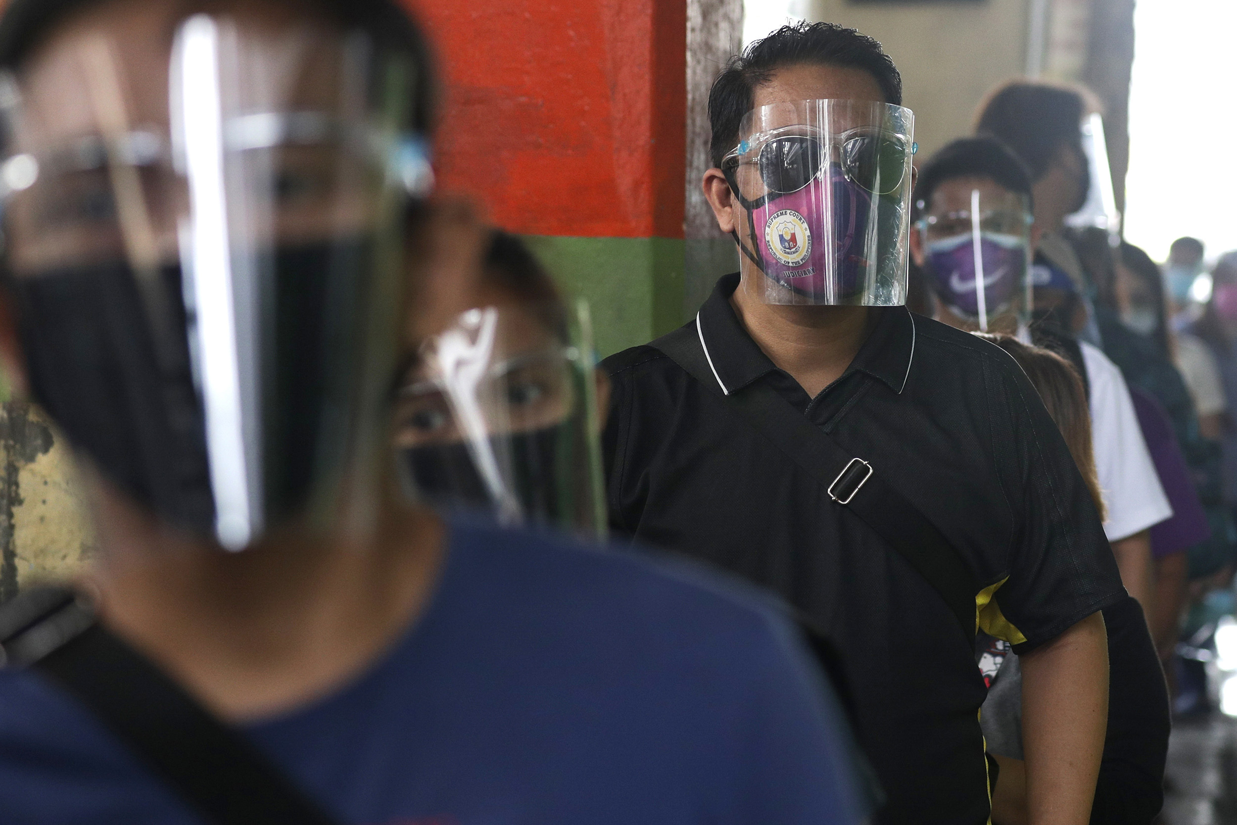 People wearing face mask and face shields to help curb the spread of COVID-19 line up for a bus ride in Caloocan city, Philippines, on Wednesday, August 19.