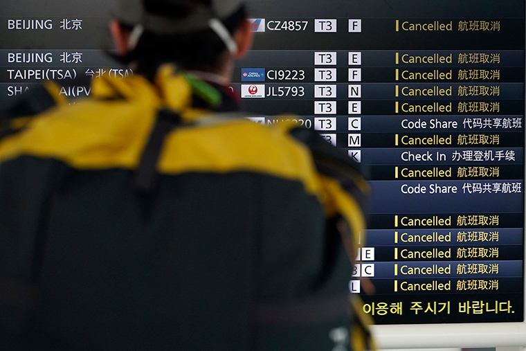 A traveler looks at canceled flights on a schedule board, some due to the coronavirus, at the Haneda International Airport in Tokyo, Wednesday, March 18.