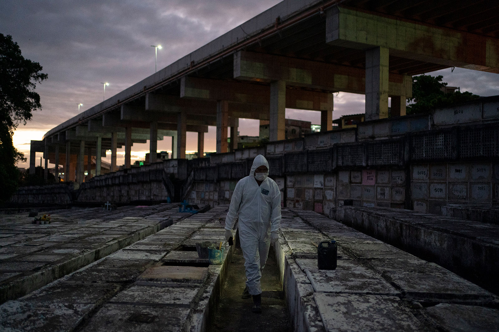 Cemetery worker Bruno Avelino walks through a graveyard in Rio de Janeiro, Brazil, on Friday, May 8.