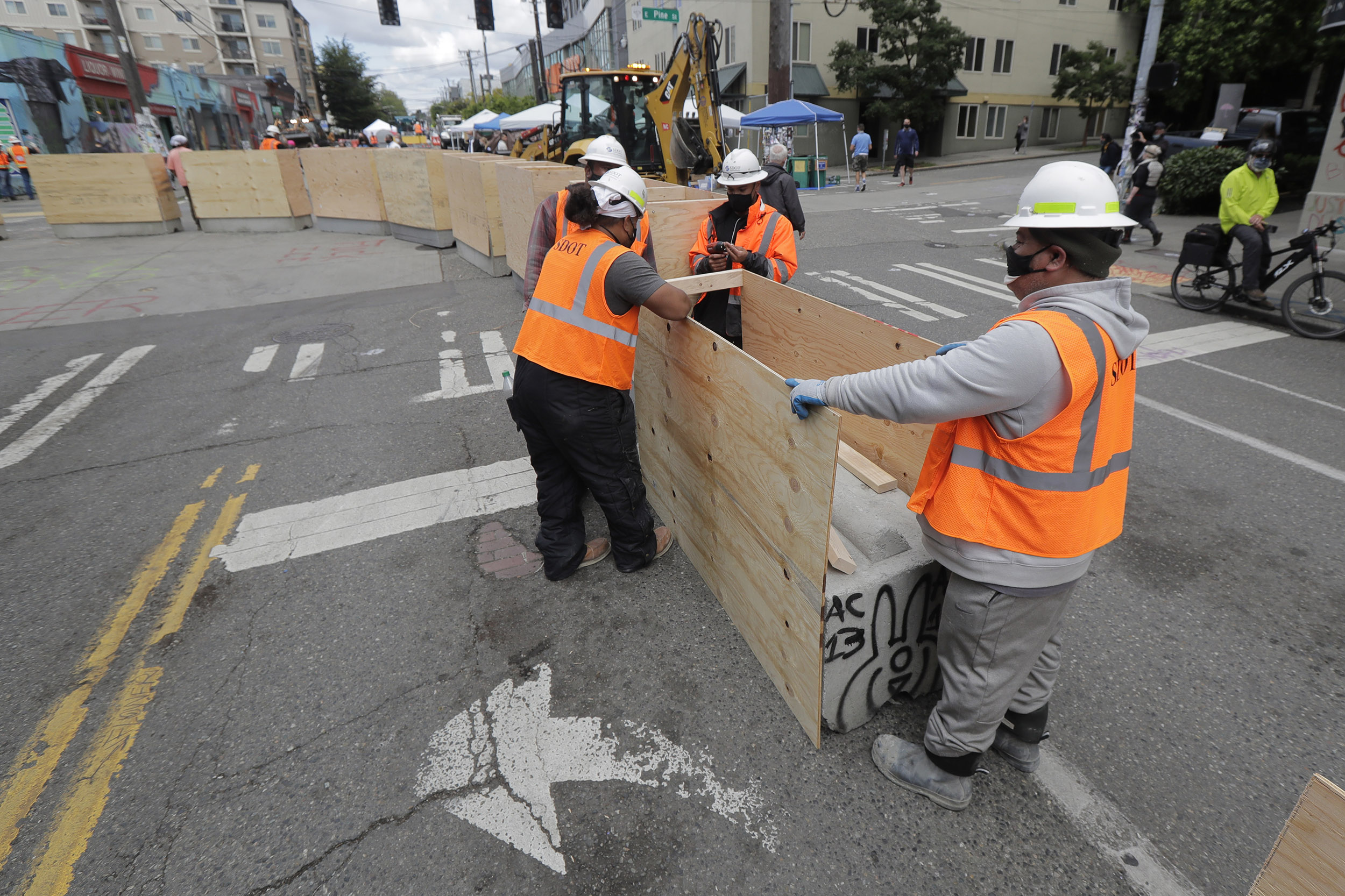 City workers install new cement and wood barricades inside what has been named the Capitol Hill Occupied Protest zone in Seattle, Washington, on Tuesday, June 16.